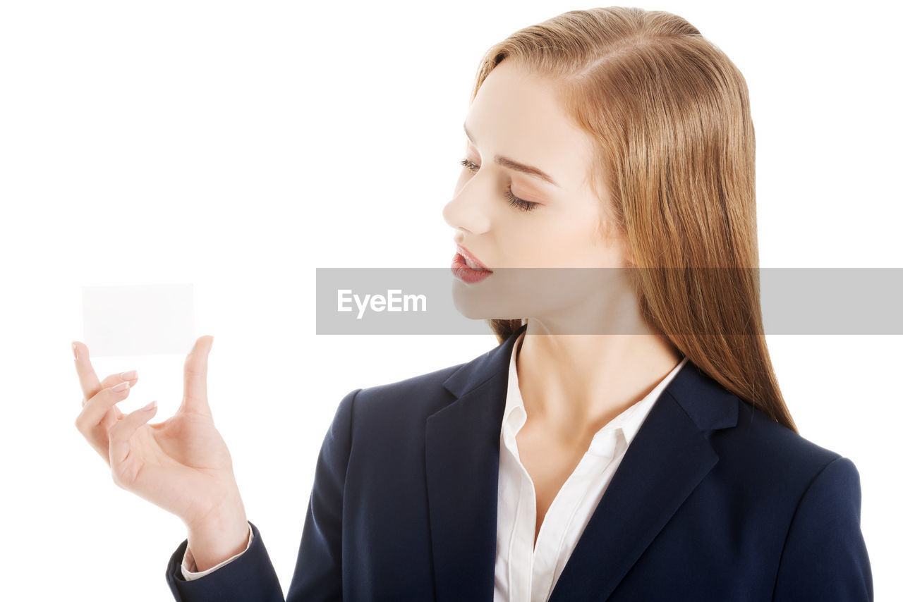 Young businesswoman holding placard against white background