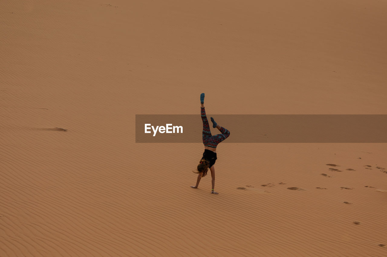 High Angle View Of Teenager Doing Handstand On Sand At Beach