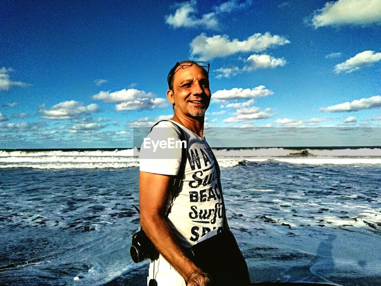 Portrait of smiling man standing at beach against sky