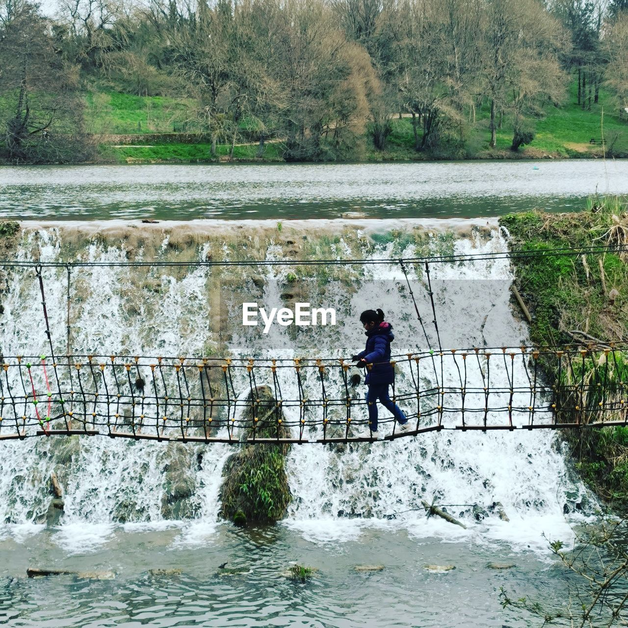 MAN STANDING BY RIVER