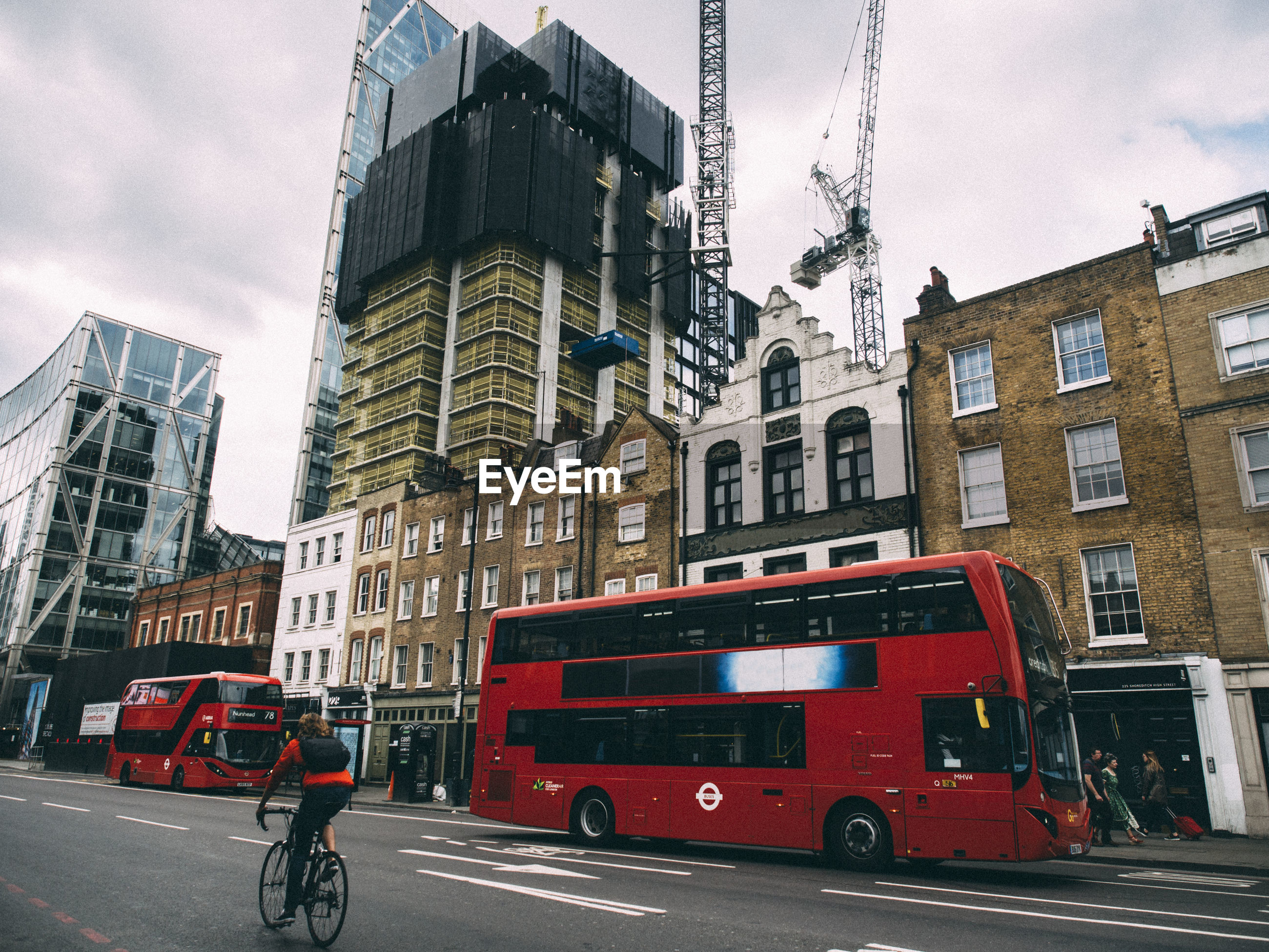 Double-decker bus on road against sky in city