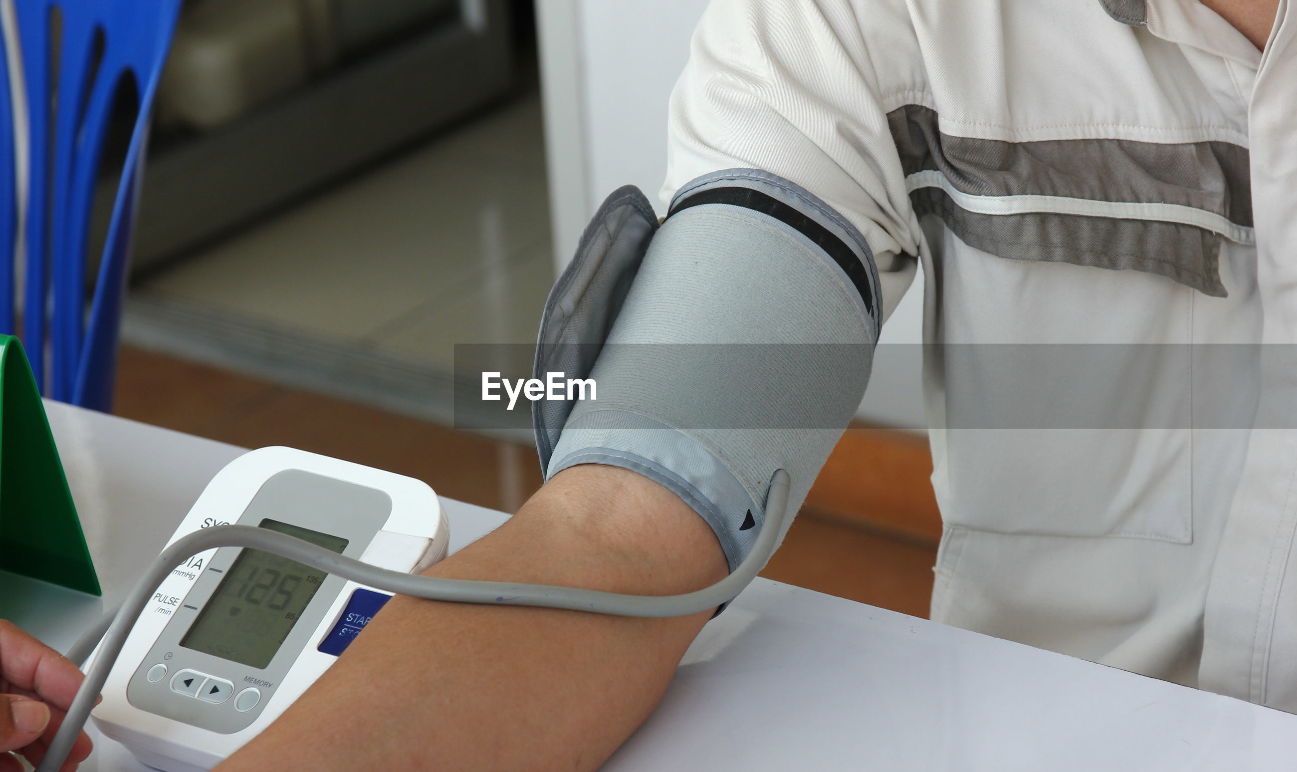 Midsection of patient examining blood pressure on table in hospital