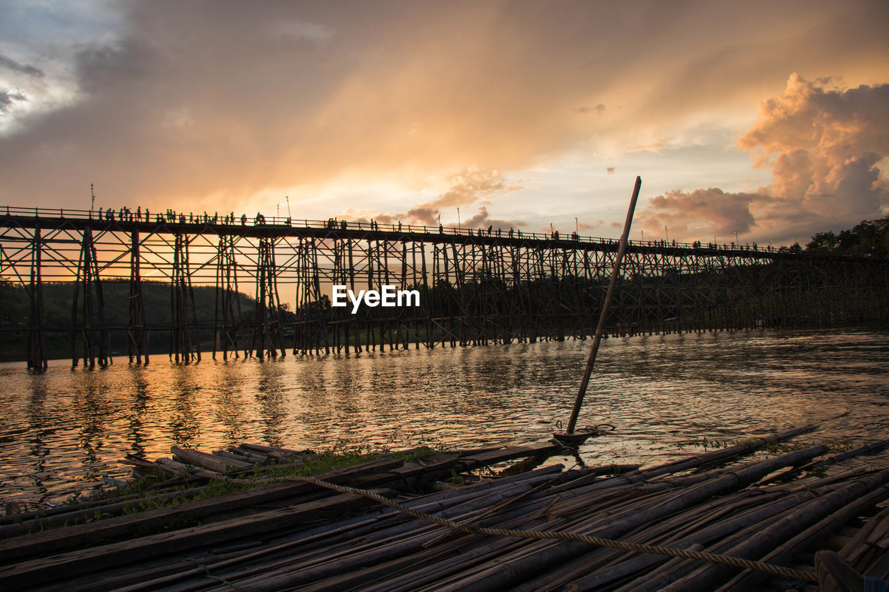 sky, cloud - sky, sunset, water, nature, beauty in nature, scenics - nature, no people, tranquil scene, tranquility, architecture, built structure, river, non-urban scene, outdoors, plant, wood - material, orange color, bridge
