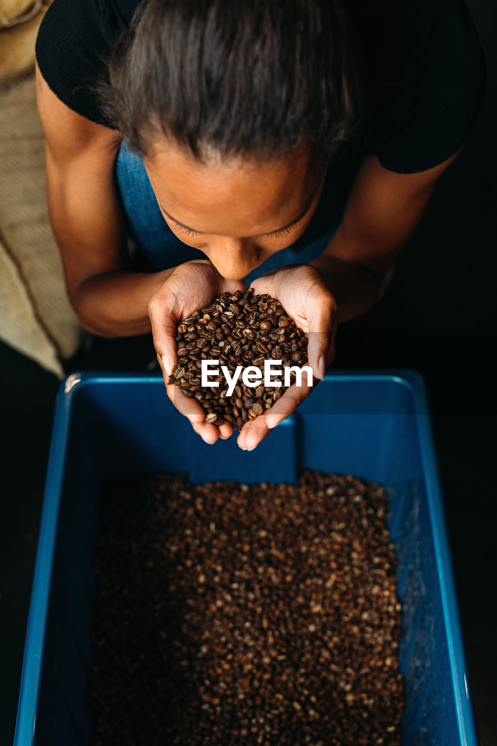High angle view of woman smelling roasted coffee beans