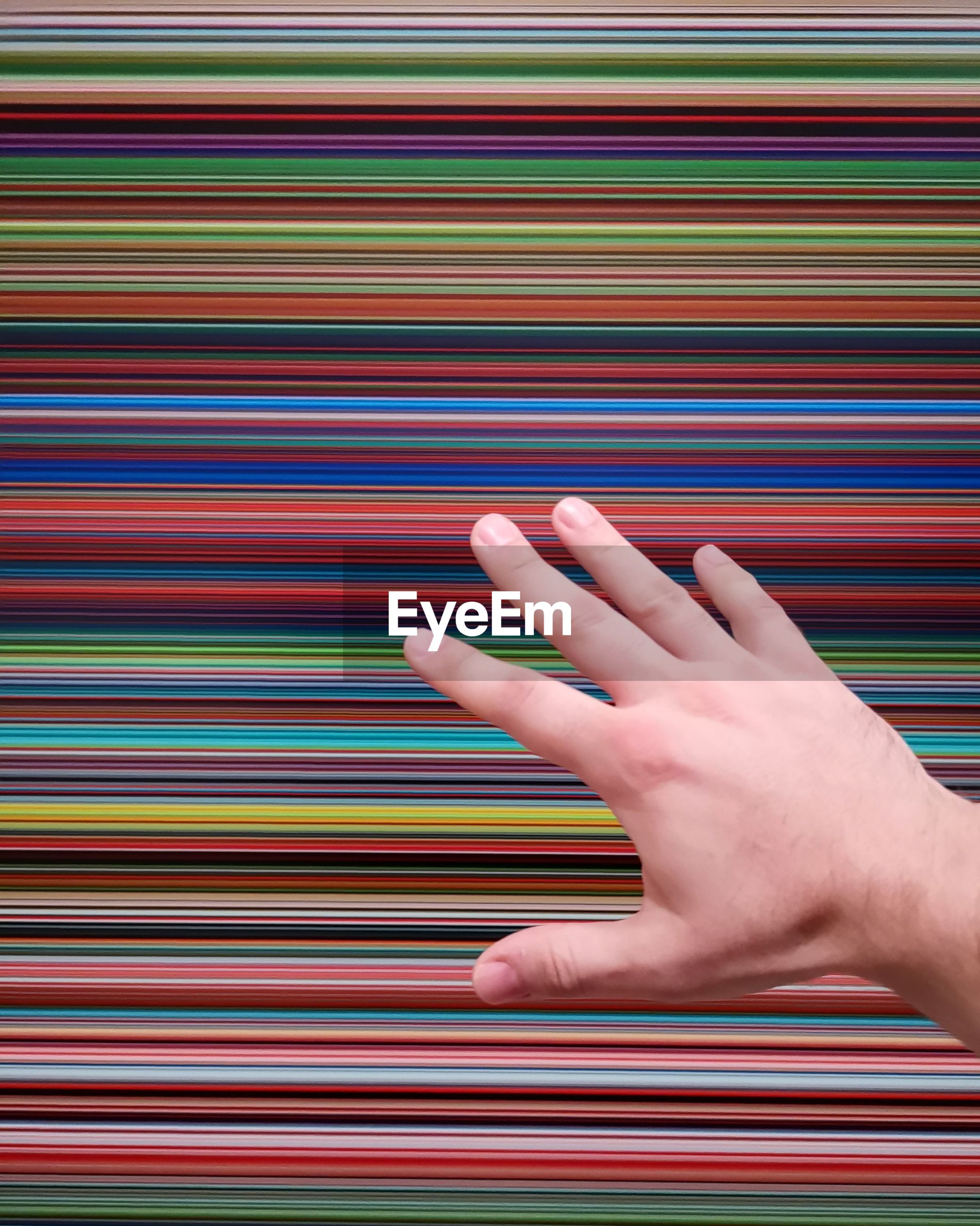 Hand against colorful pattern