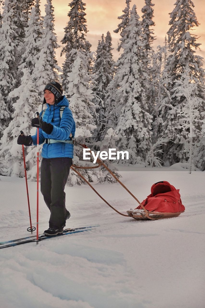 winter, snow, cold temperature, winter sport, tree, sport, mountain, warm clothing, leisure activity, nature, real people, skiing, holiday, full length, day, ski pole, lifestyles, beauty in nature, clothing, mountain range, ski-wear, outdoors