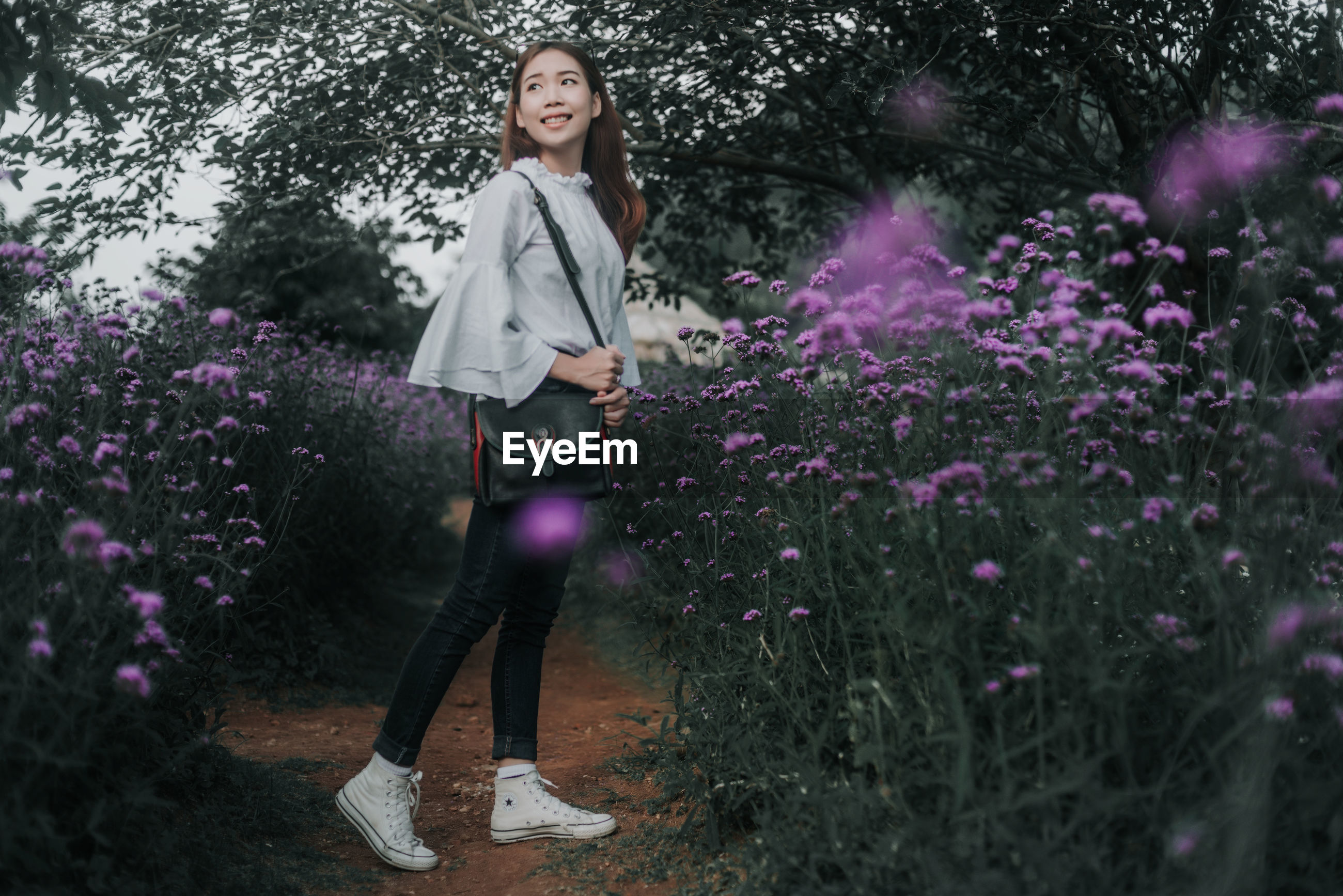 PORTRAIT OF A BEAUTIFUL YOUNG WOMAN STANDING ON PURPLE FLOWERING PLANTS