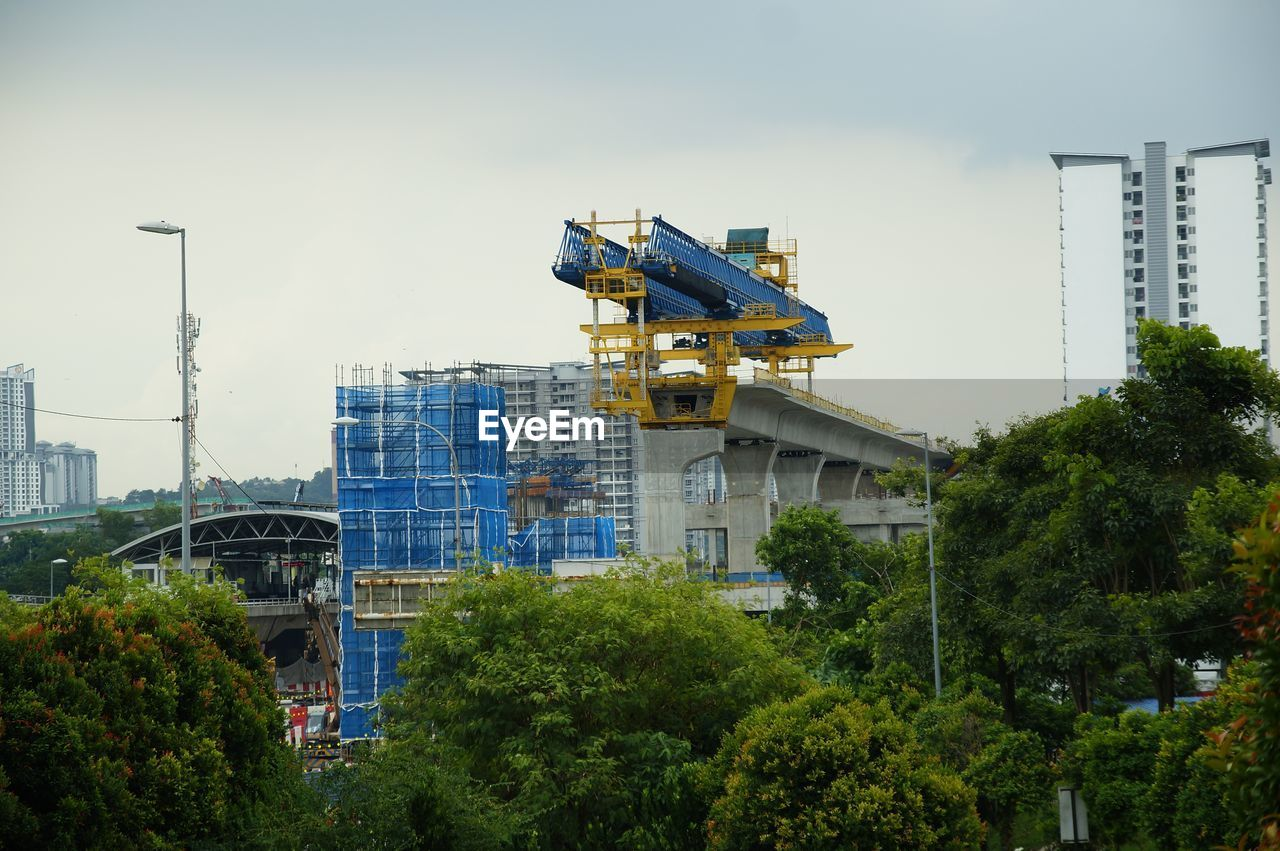 LOW ANGLE VIEW OF CRANE AMIDST TREES AND BUILDINGS AGAINST SKY