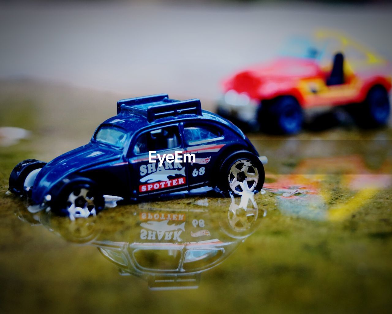 toy, toy car, focus on foreground, no people, close-up, childhood, land vehicle, outdoors, day