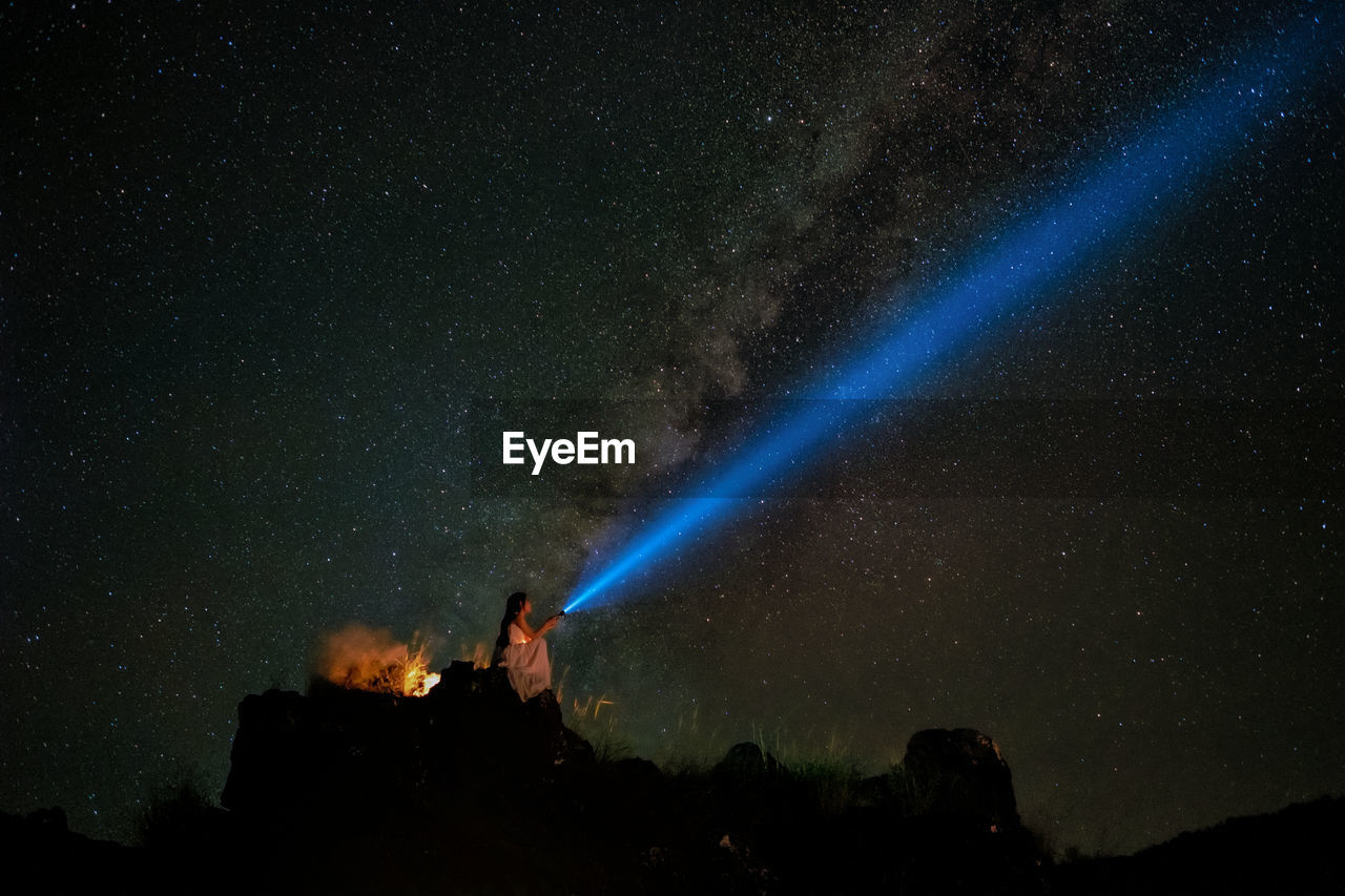 Low Angle View Of Woman With Flashlight Sitting On Cliff Against Sky At Night