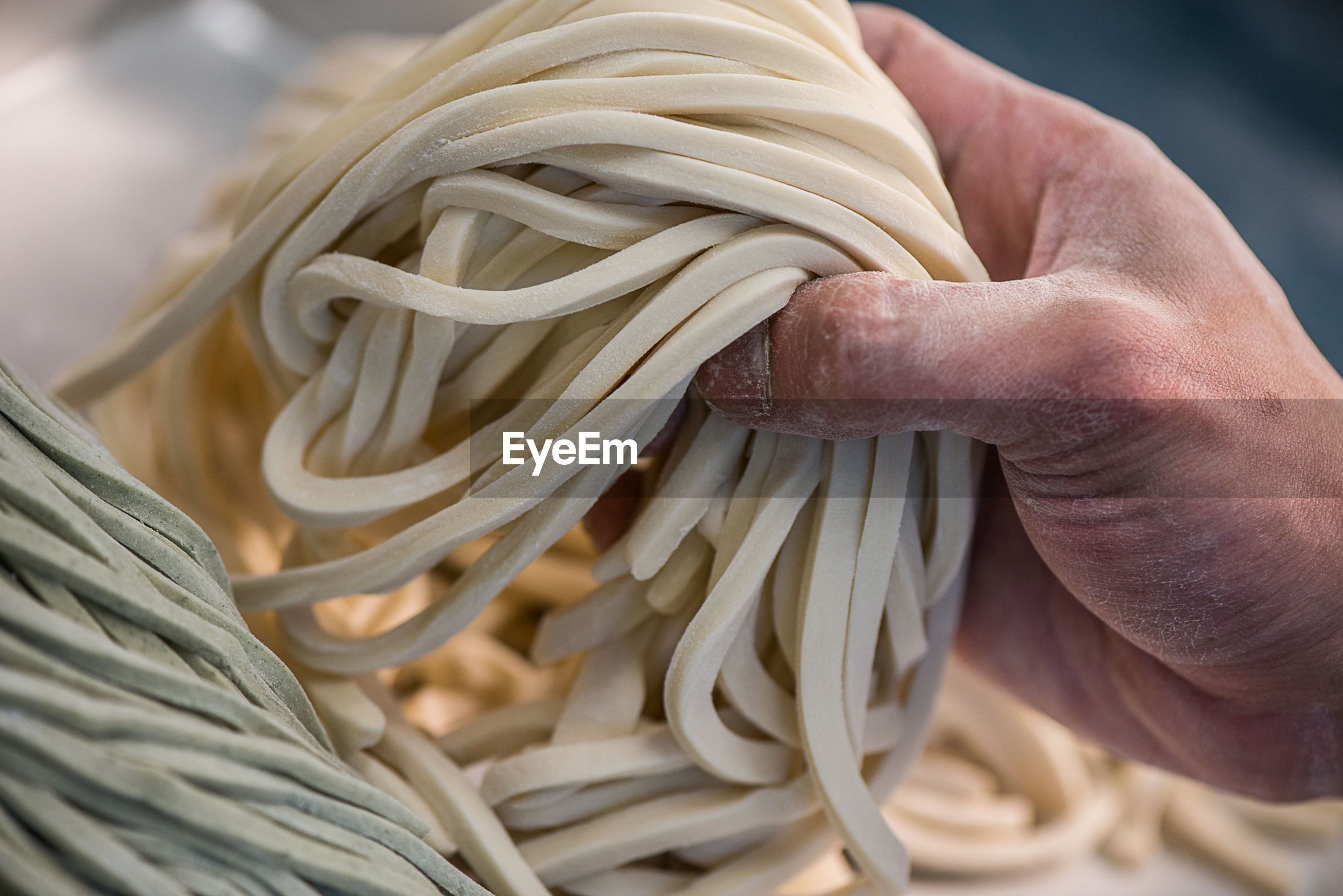 Close-up of hand holding homemade noodles