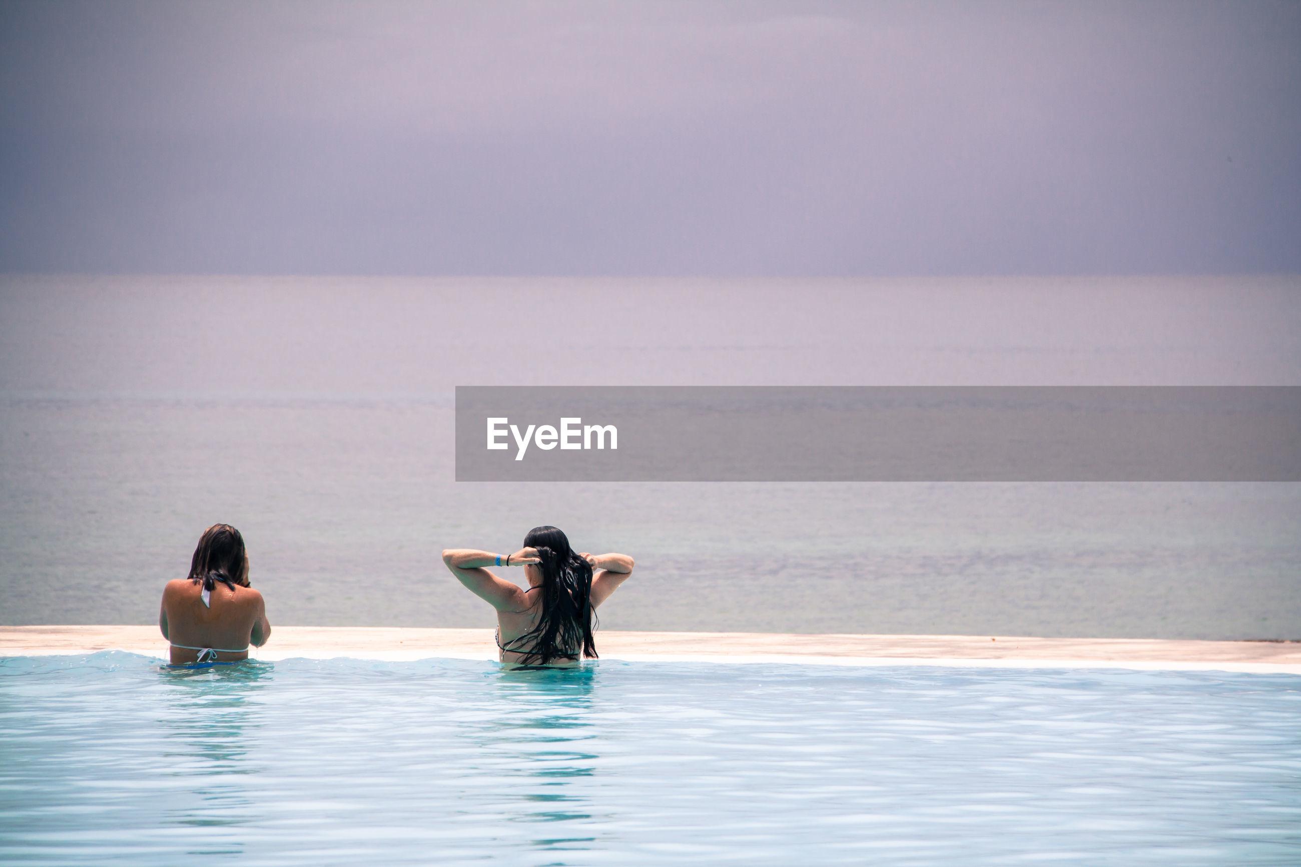 Rear view of women in infinity pool against sea