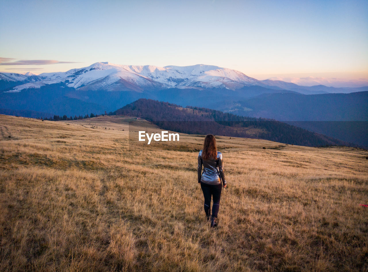 Rear View Of Woman Walking On Grassy Mountain During Sunset