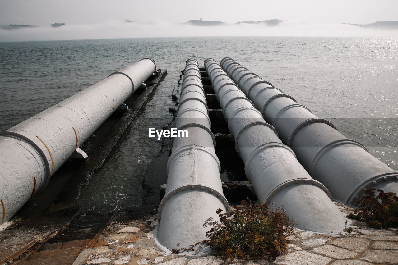 Industrial pipes over sea against sky