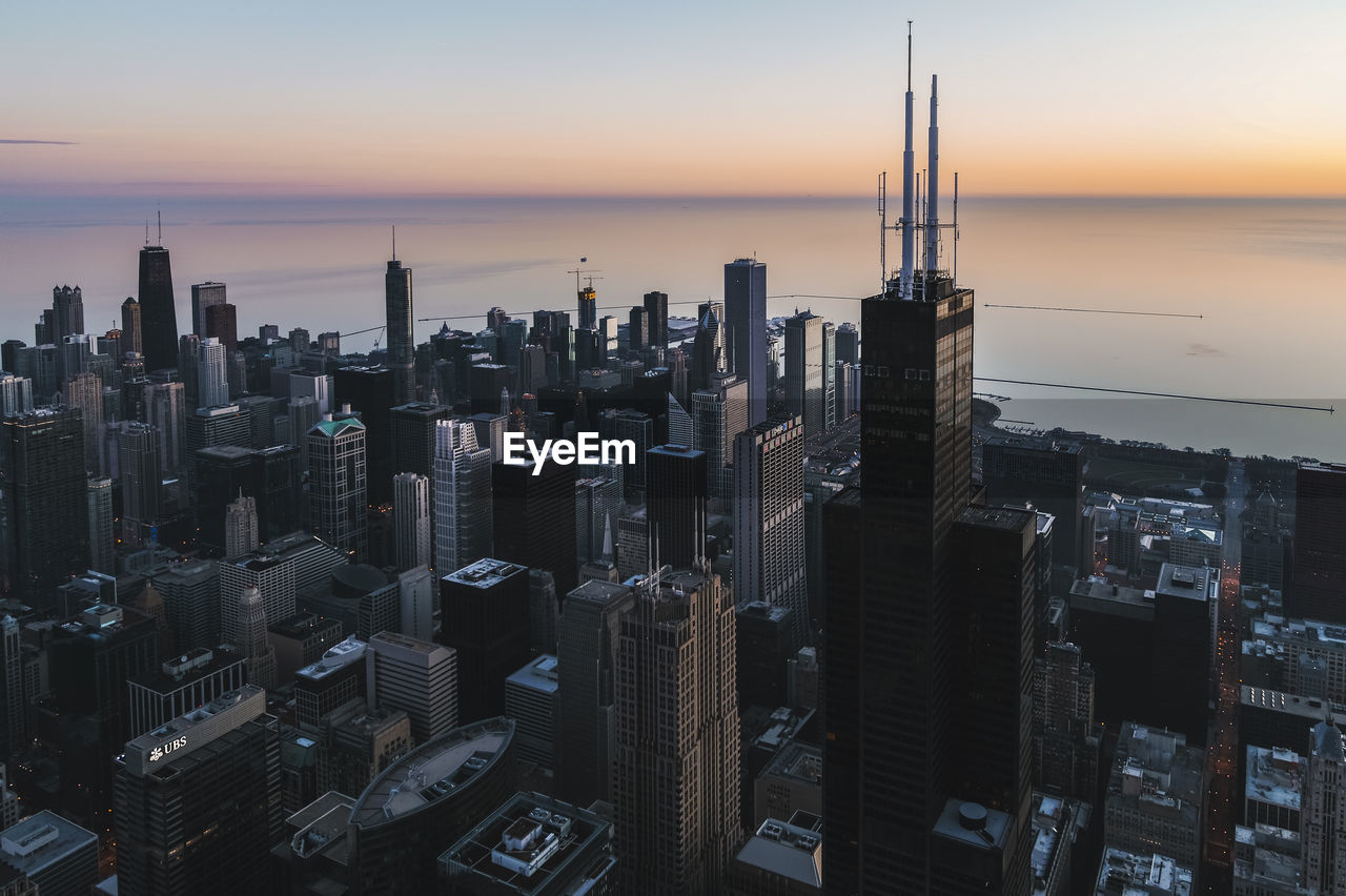 Aerial View Of Buildings In City Against By Lake Sky During Sunset