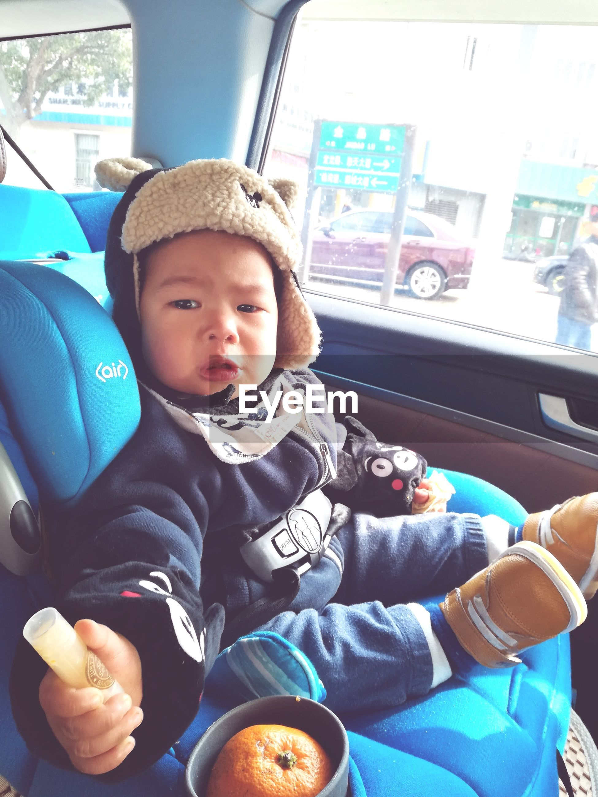 Portrait of cute baby boy sitting in car