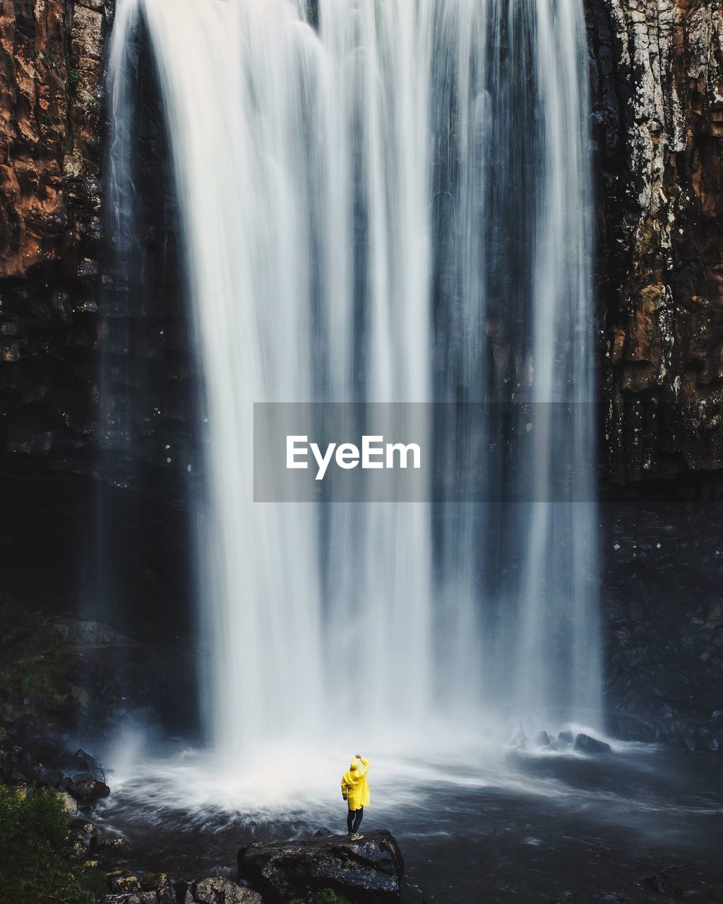 Person Wearing Yellow Raincoat Looking At Majestic Waterfall In Forest