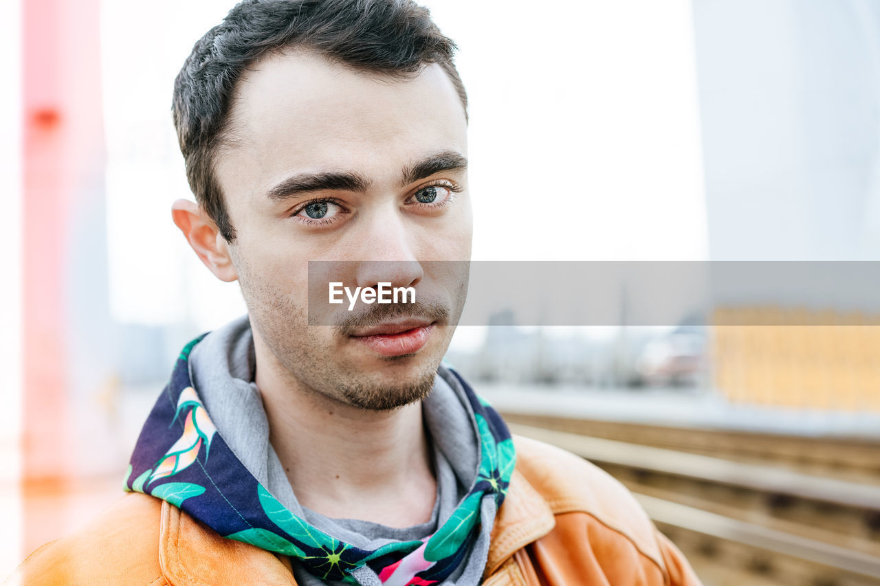 Portrait Of Young Man Standing At Railroad Station Platform