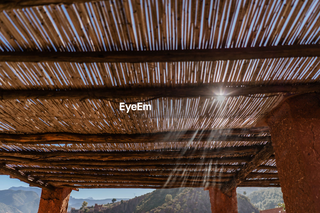 architecture, no people, indoors, built structure, pattern, low angle view, roof, day, ceiling, sunlight, wood - material, metal, building, industry, factory, nature, architectural column, brown, close-up, roof beam