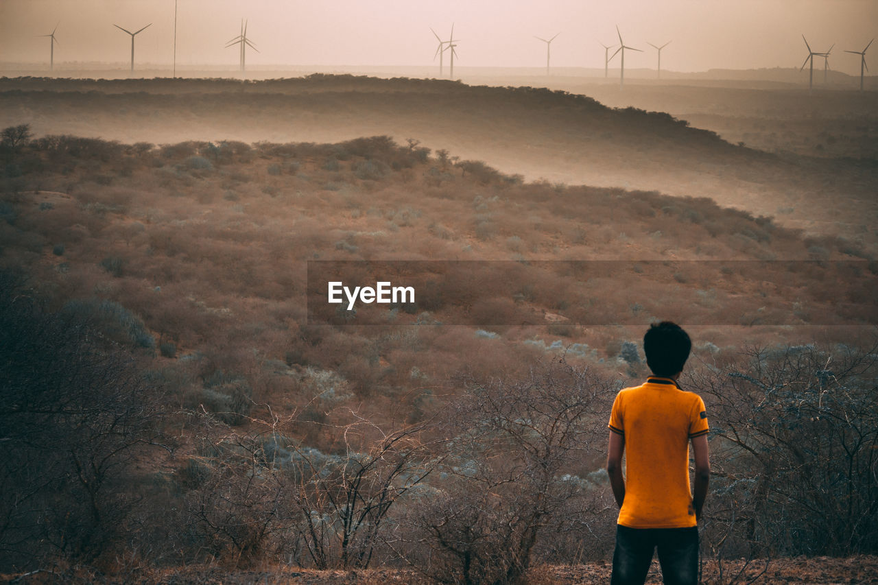 rear view, environment, fuel and power generation, land, nature, wind turbine, turbine, standing, real people, environmental conservation, landscape, orange color, renewable energy, beauty in nature, sky, one person, three quarter length, wind power, field, lifestyles, outdoors, looking at view
