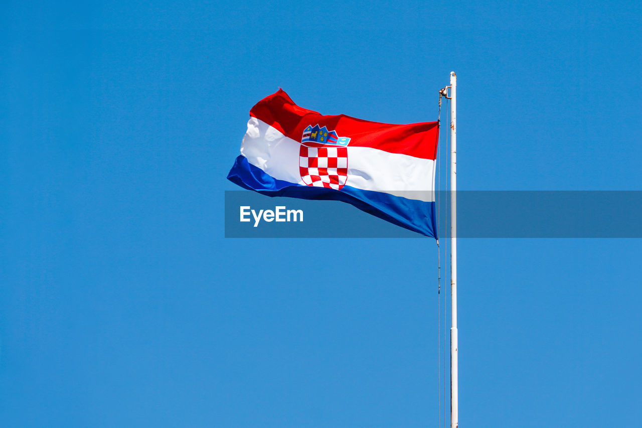 Low angle view of croatian flag against clear blue sky.