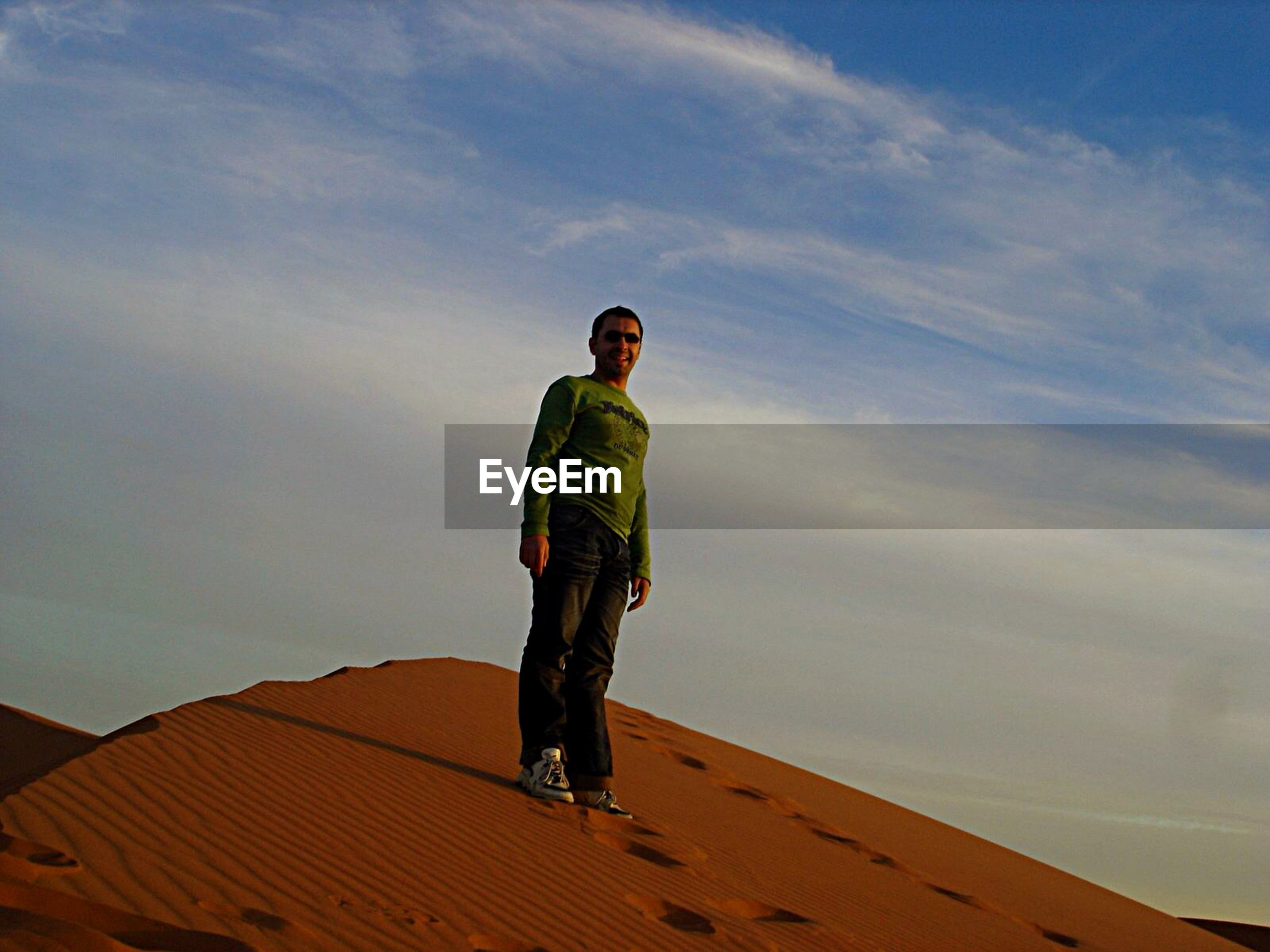 Low angle view of happy man standing on sand dune against sky