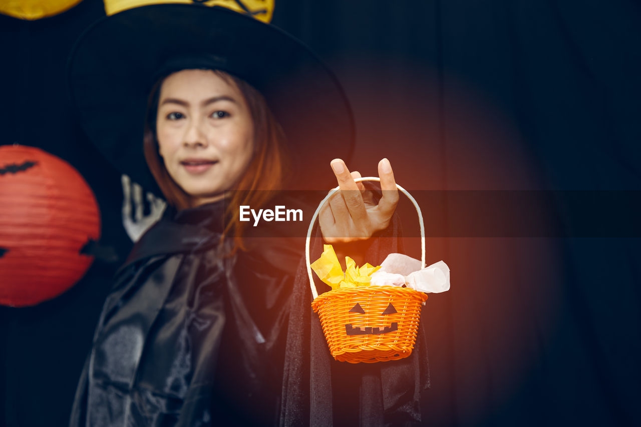 one person, front view, real people, halloween, clothing, leisure activity, looking at camera, standing, celebration, women, hat, portrait, representation, lifestyles, smiling, childhood, waist up, holding, witch, jack o' lantern