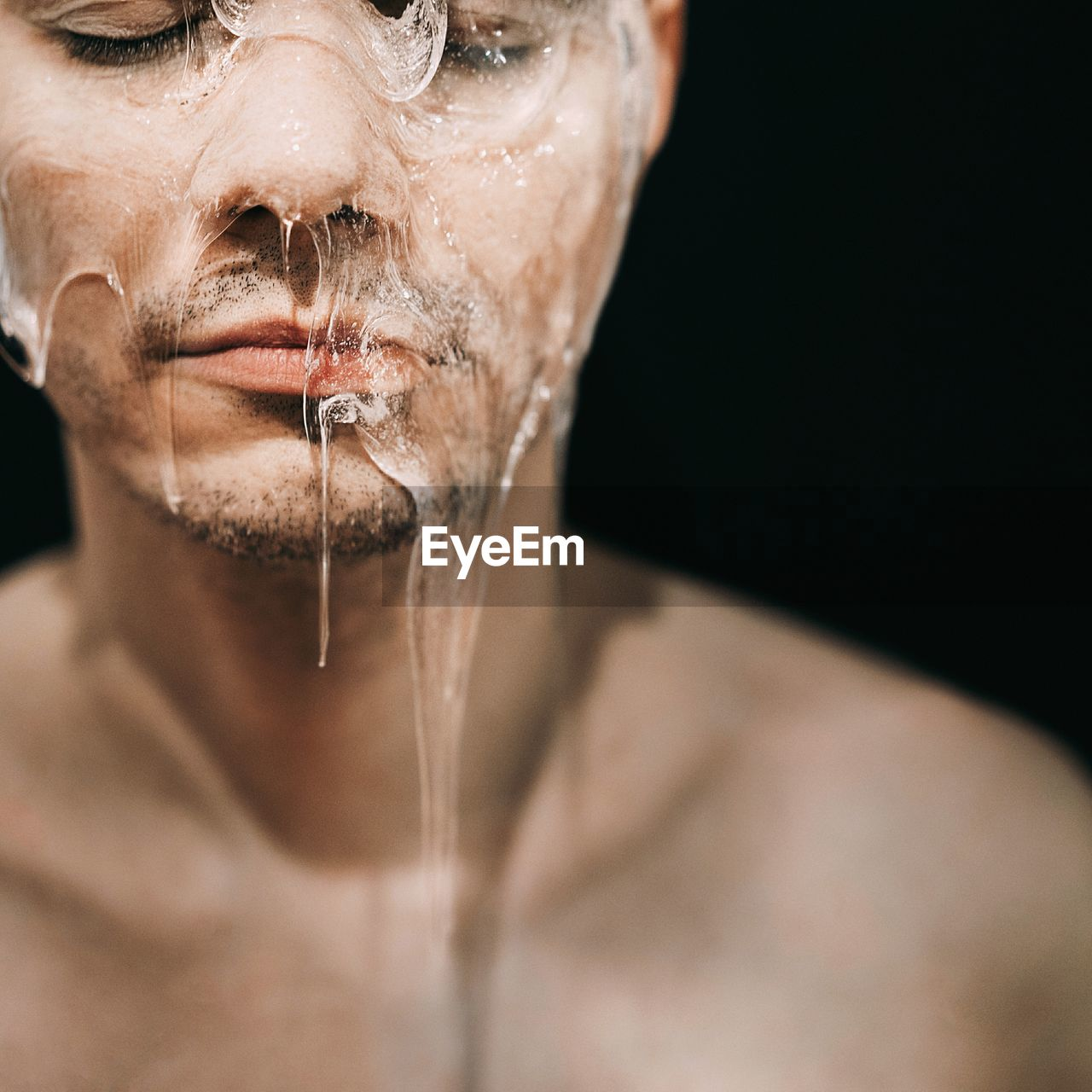 Close-Up Of Shirtless Man With Ice On Face Against Black Background