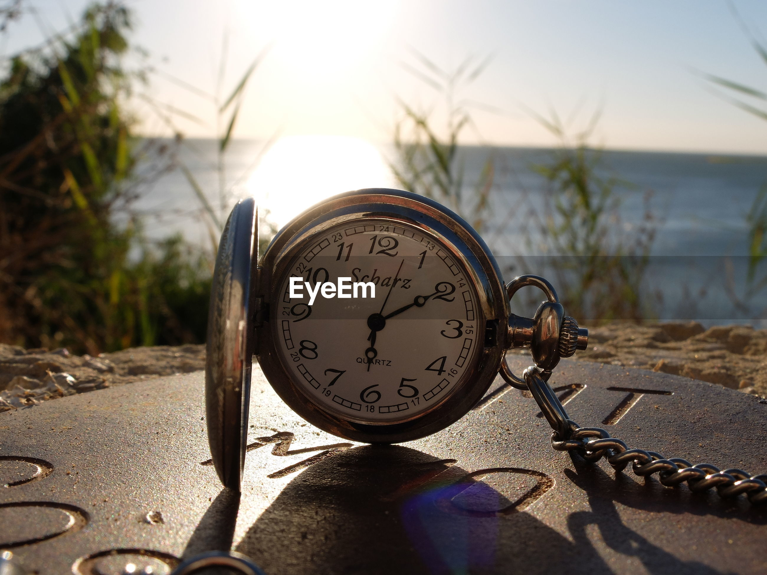 number, sunlight, sand, sea, no people, close-up, text, beach, outdoors, focus on foreground, day, shadow, time, navigational compass, nature, sky, water, minute hand