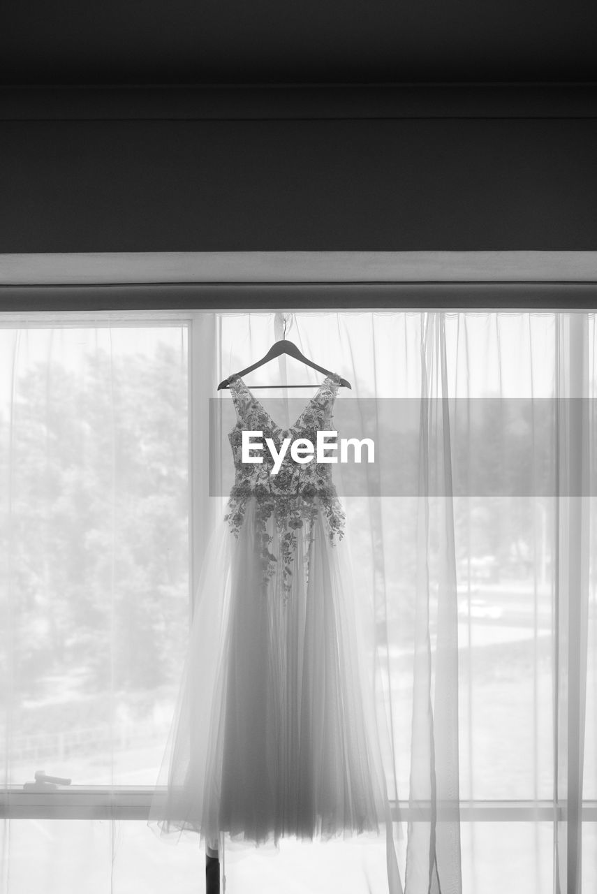 Wedding gown hanging by curtain on wall