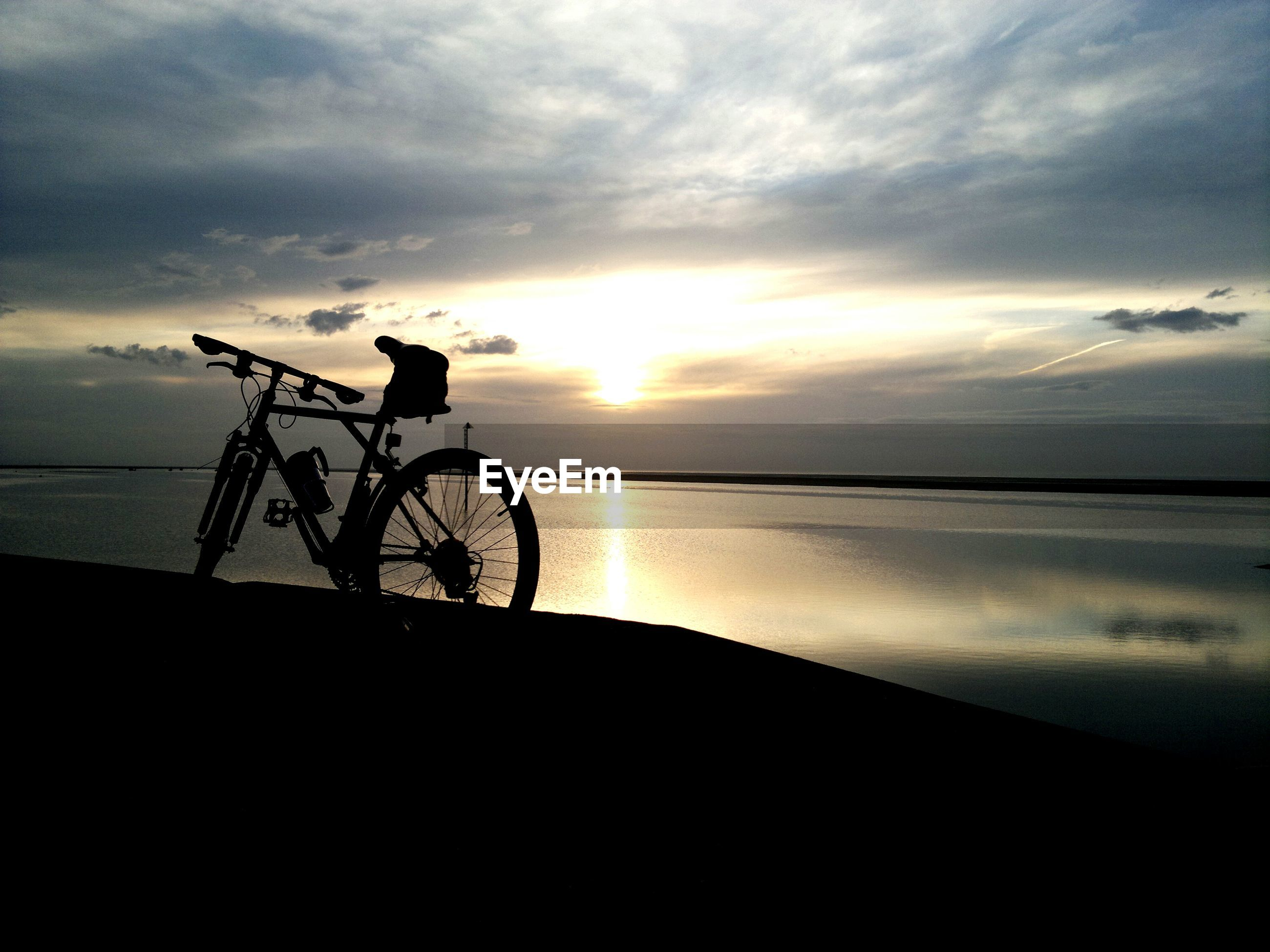 Scenic view of sea and bike at sunset