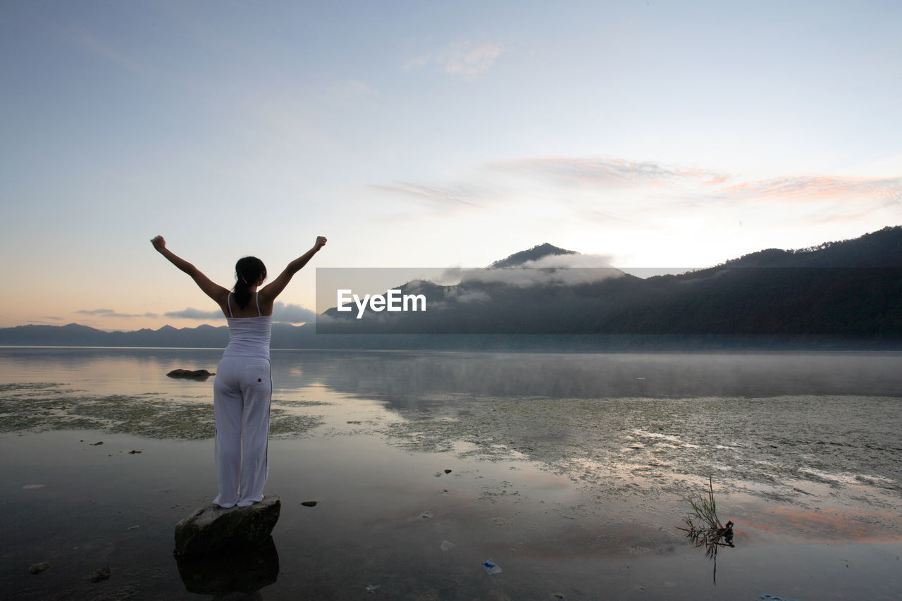 Rear View Of Woman On Lake Against Sky