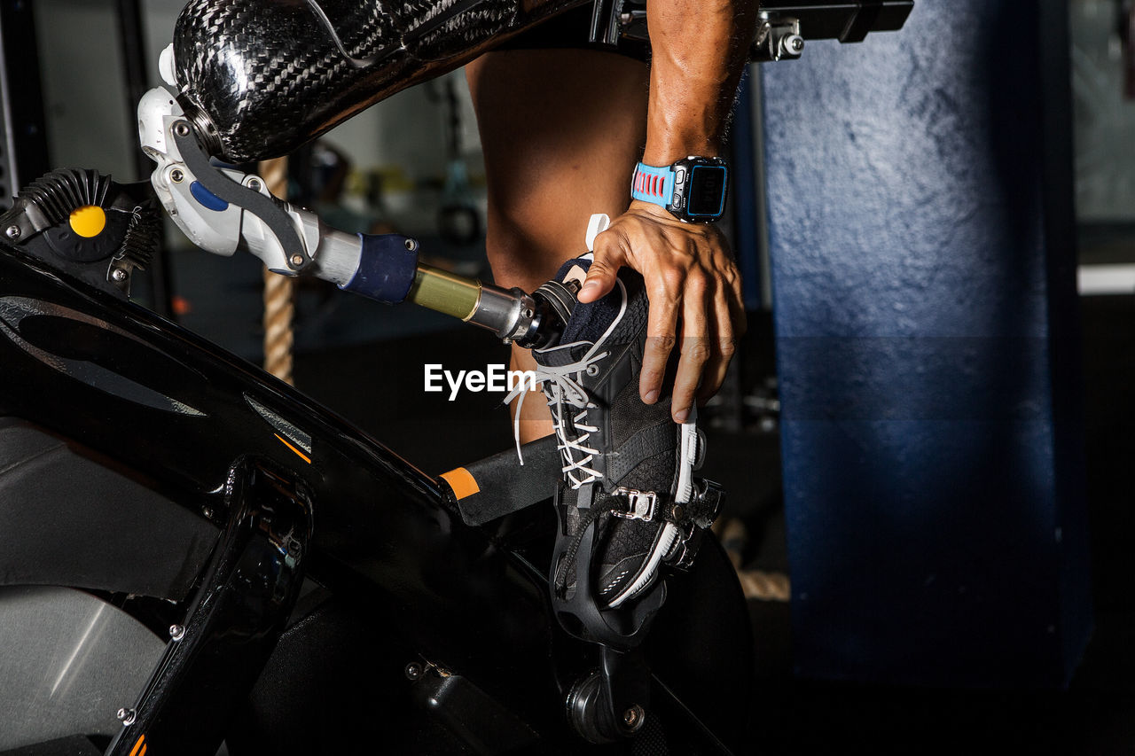 Low section of disabled man touching artificial limb while exercising in gym