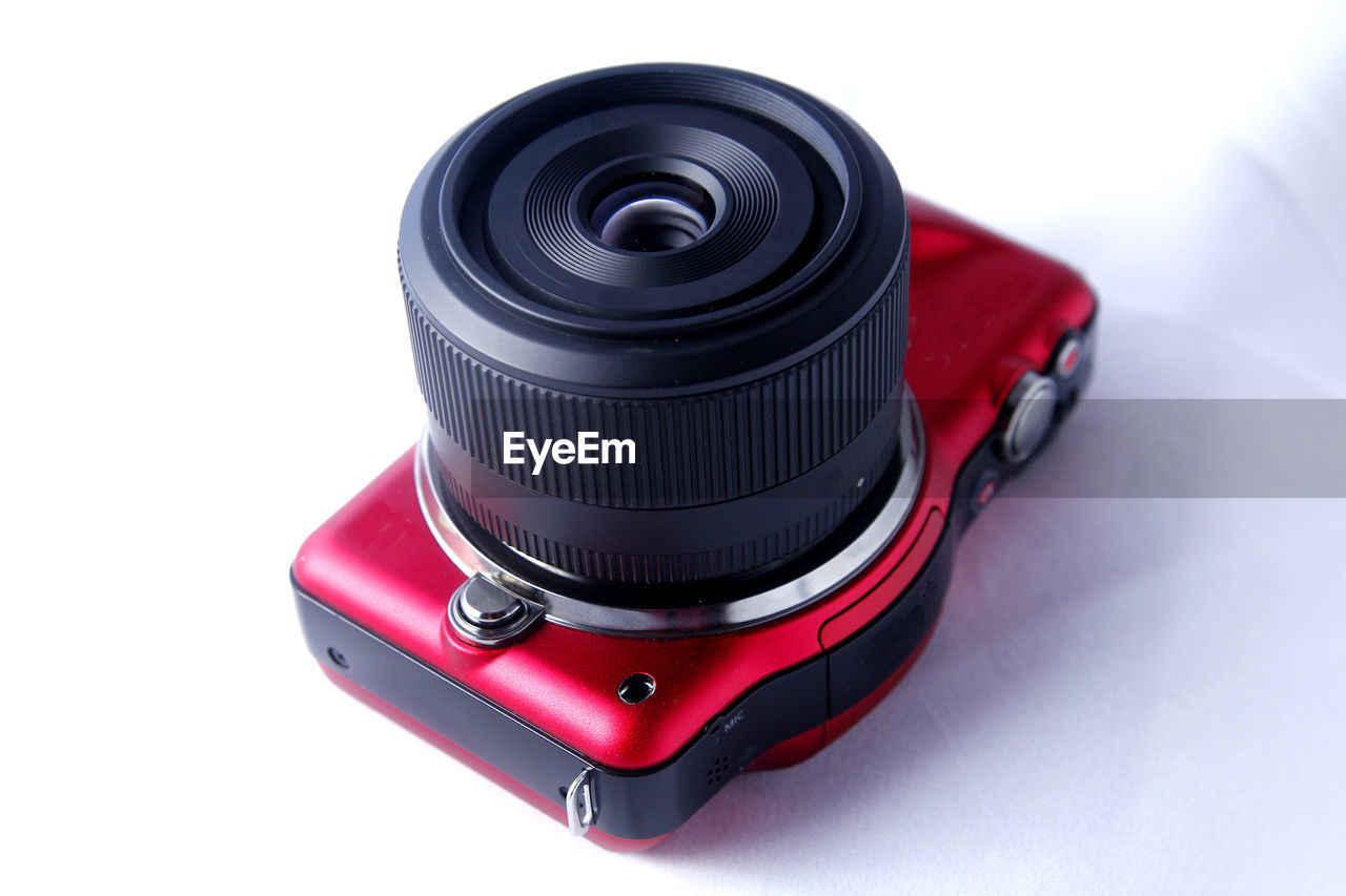 technology, photography themes, camera - photographic equipment, studio shot, white background, black color, close-up, indoors, cut out, still life, photographic equipment, lens - optical instrument, single object, red, no people, high angle view, retro styled, focus on foreground, copy space, digital camera