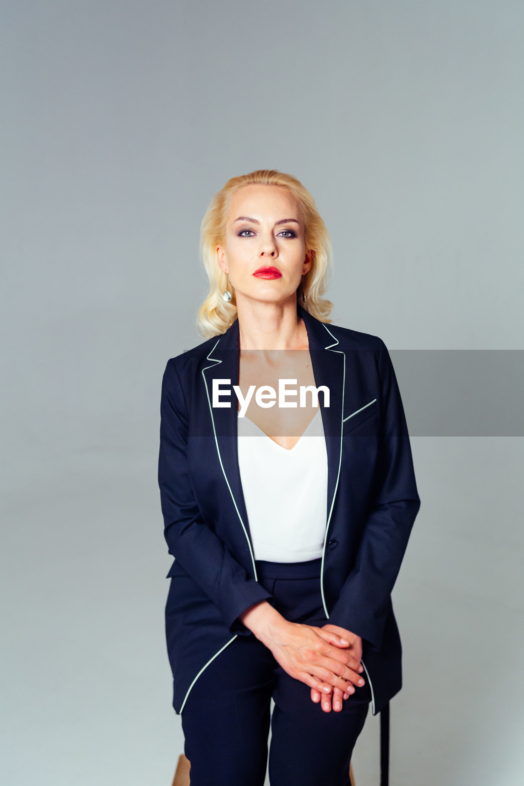 Portrait of confident businesswoman sitting on stool against white background