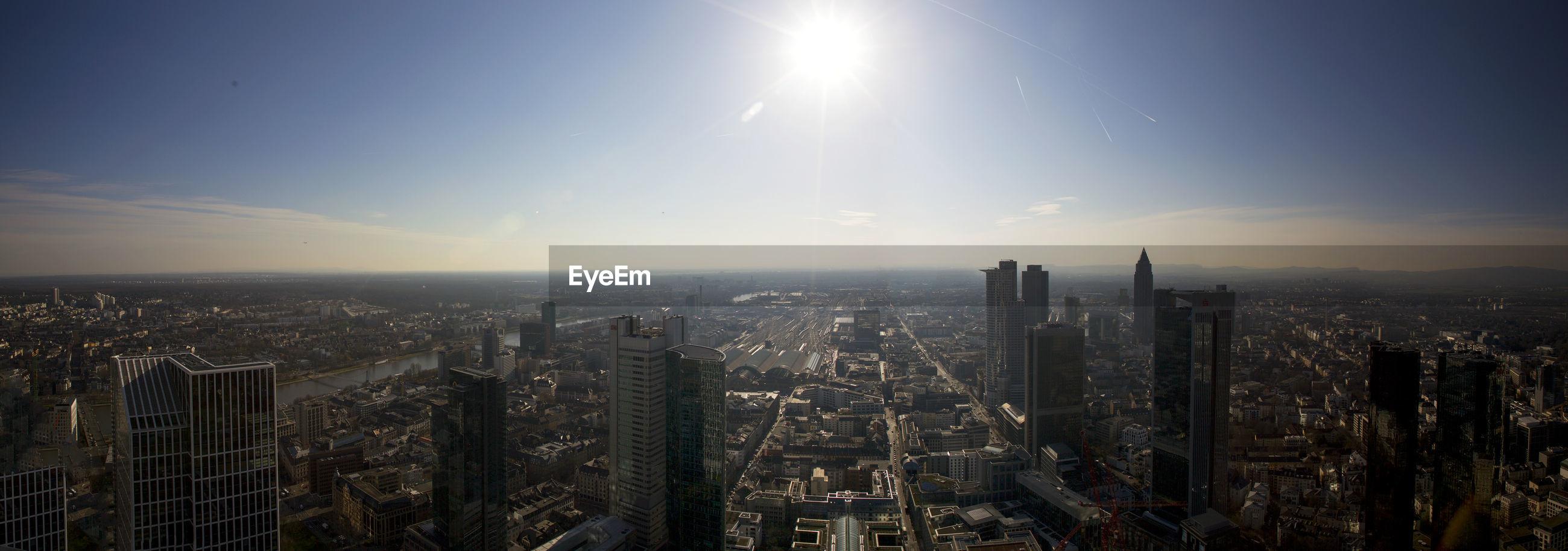 AERIAL VIEW OF MODERN BUILDINGS IN CITY AGAINST BRIGHT SKY