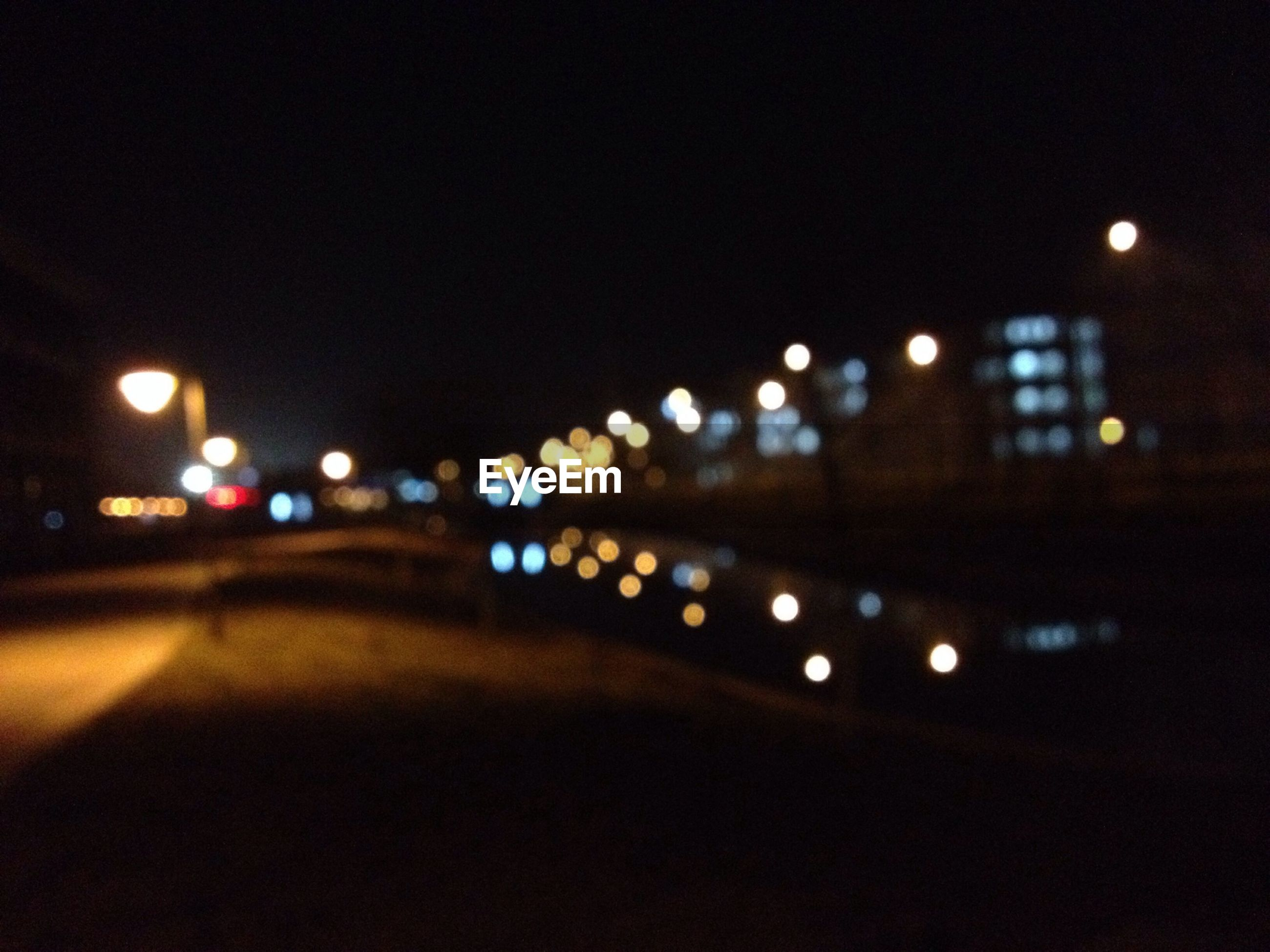 illuminated, night, lighting equipment, street light, defocused, street, transportation, road, the way forward, city, building exterior, light - natural phenomenon, architecture, built structure, dark, no people, car, outdoors, copy space, clear sky