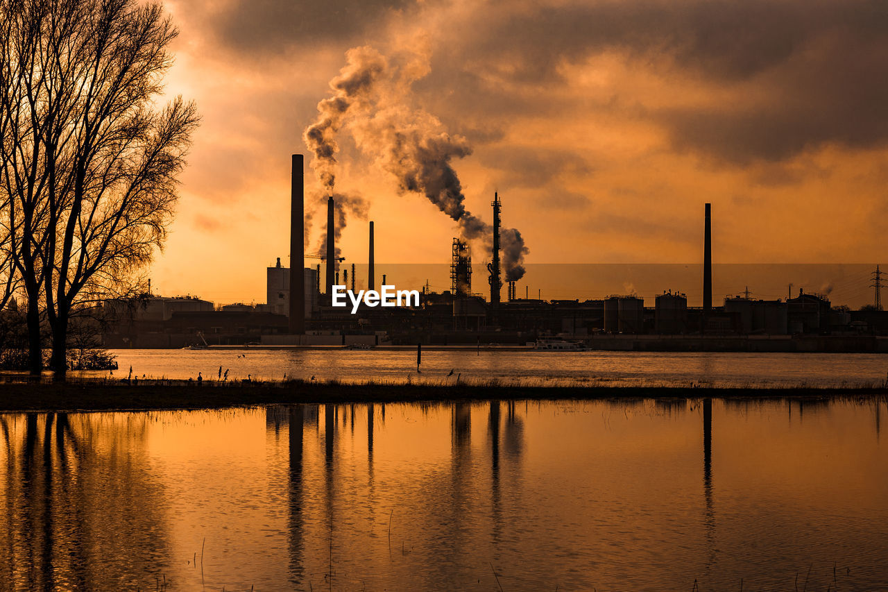 factory, sky, industry, smoke stack, sunset, building exterior, smoke - physical structure, water, reflection, built structure, waterfront, architecture, emitting, environmental issues, cloud - sky, pollution, orange color, nature, environment, no people, air pollution, outdoors, fumes, atmospheric