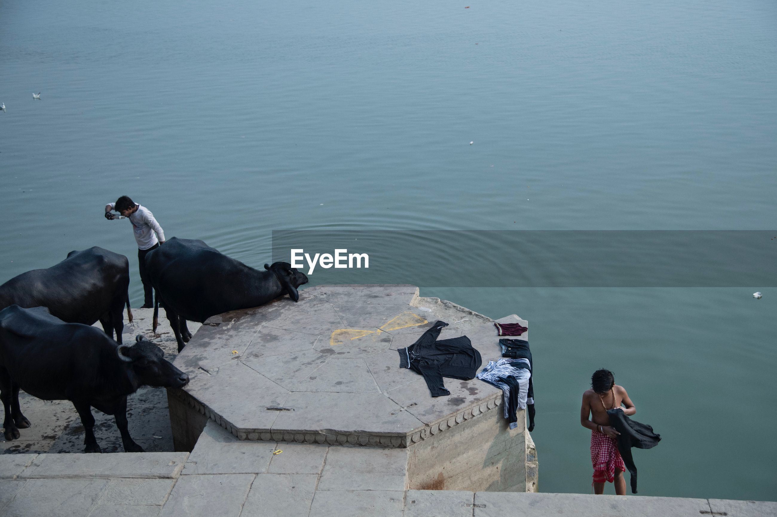 HIGH ANGLE VIEW OF PEOPLE ON SEA BY SHORE