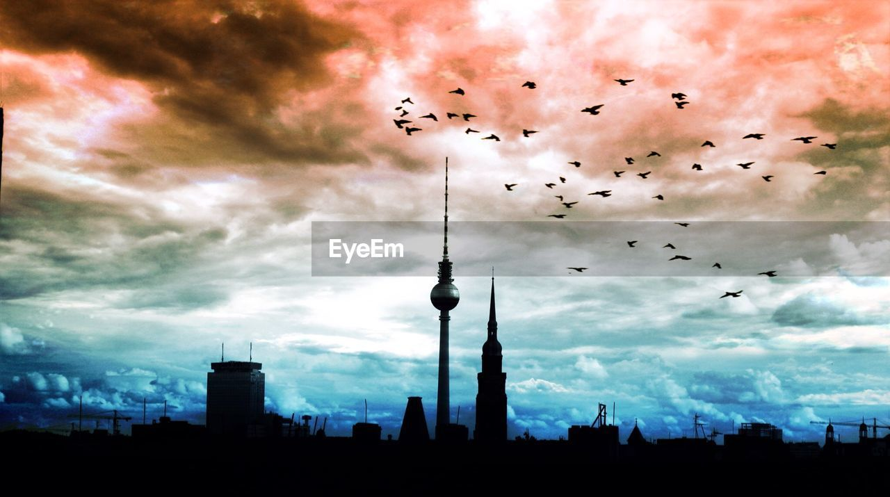 cloud - sky, sky, architecture, building exterior, tall - high, built structure, tower, large group of animals, bird, city, flock of birds, animal themes, skyscraper, silhouette, flying, travel destinations, mid-air, outdoors, no people, urban skyline, sunset, nature, cityscape, animals in the wild, modern, day