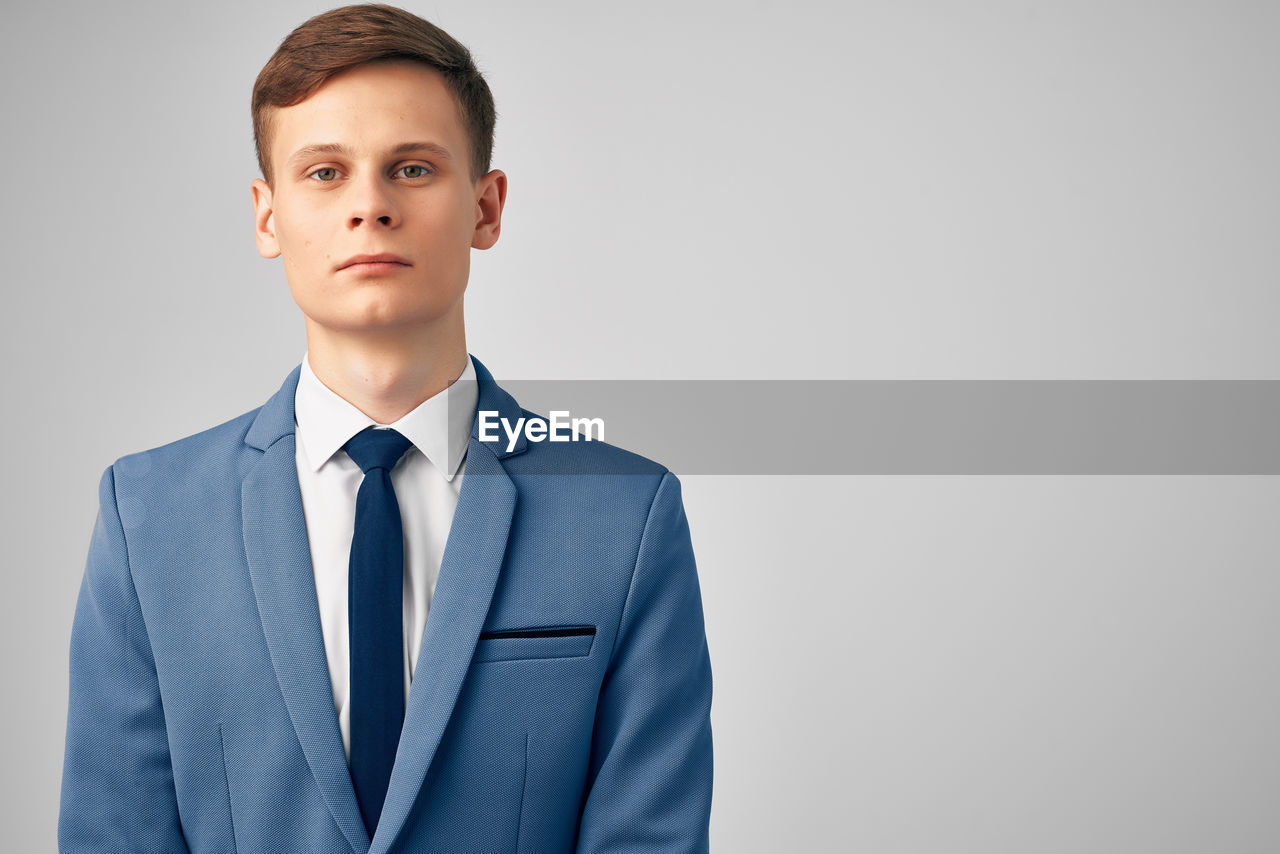 PORTRAIT OF A YOUNG MAN AGAINST GRAY BACKGROUND