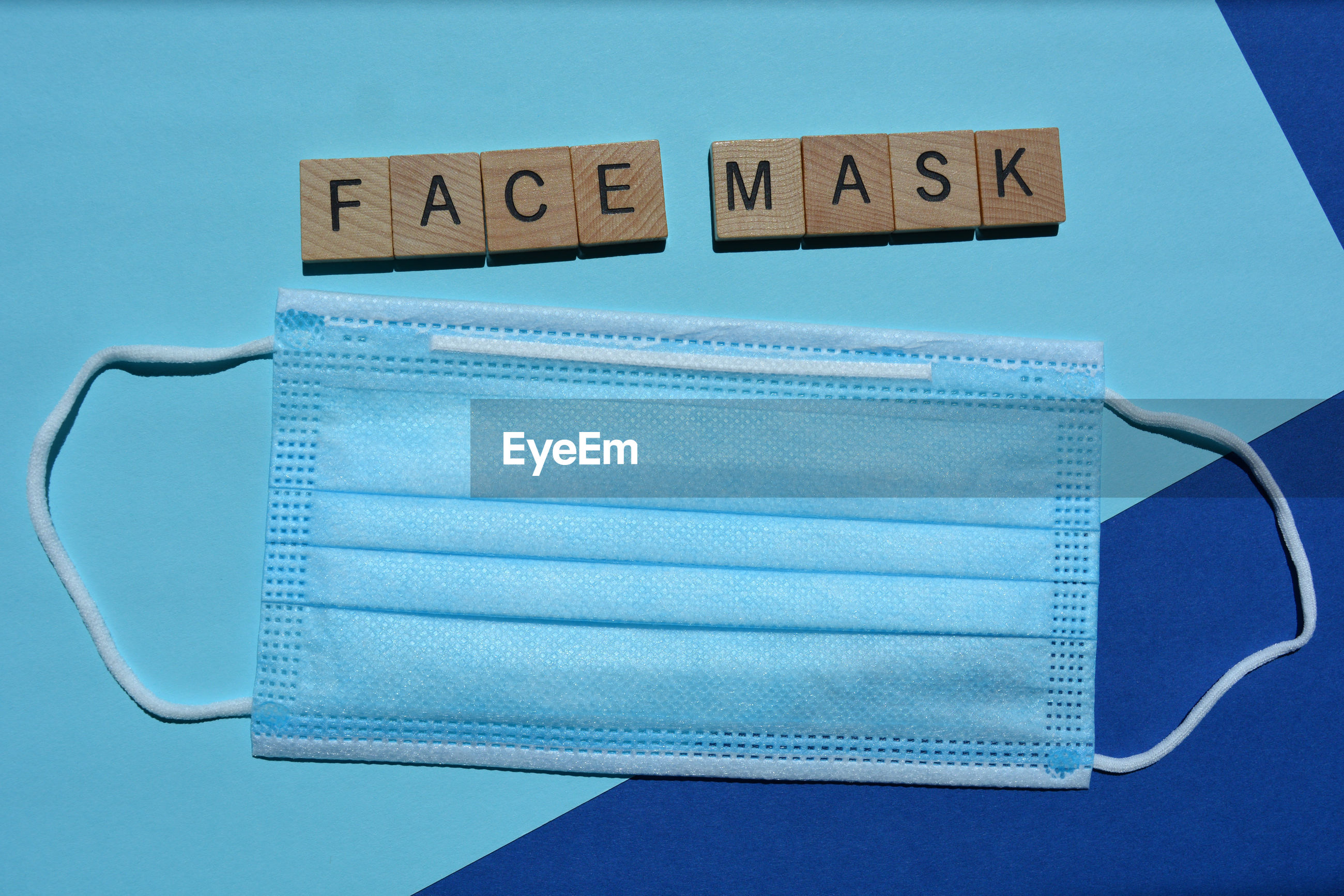 Face mask, word and a disposable 3 ply face mask with elastic ear loops isolated on blue background