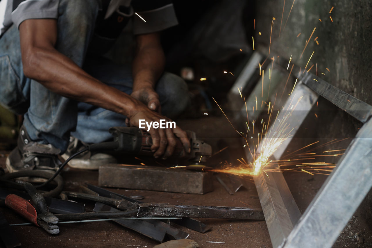 Low Section Of Male Worker Grinding At Workshop