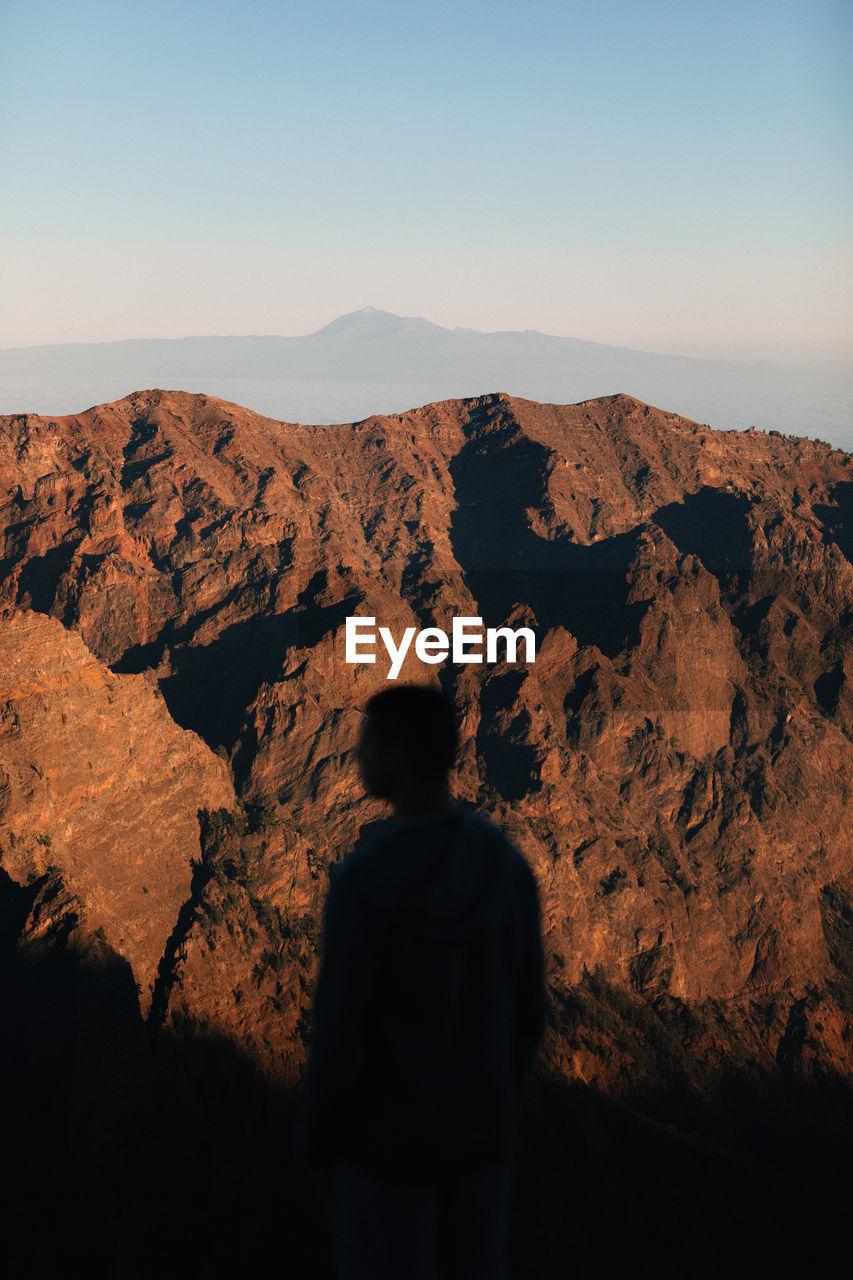 REAR VIEW OF MAN LOOKING AT MOUNTAIN RANGE