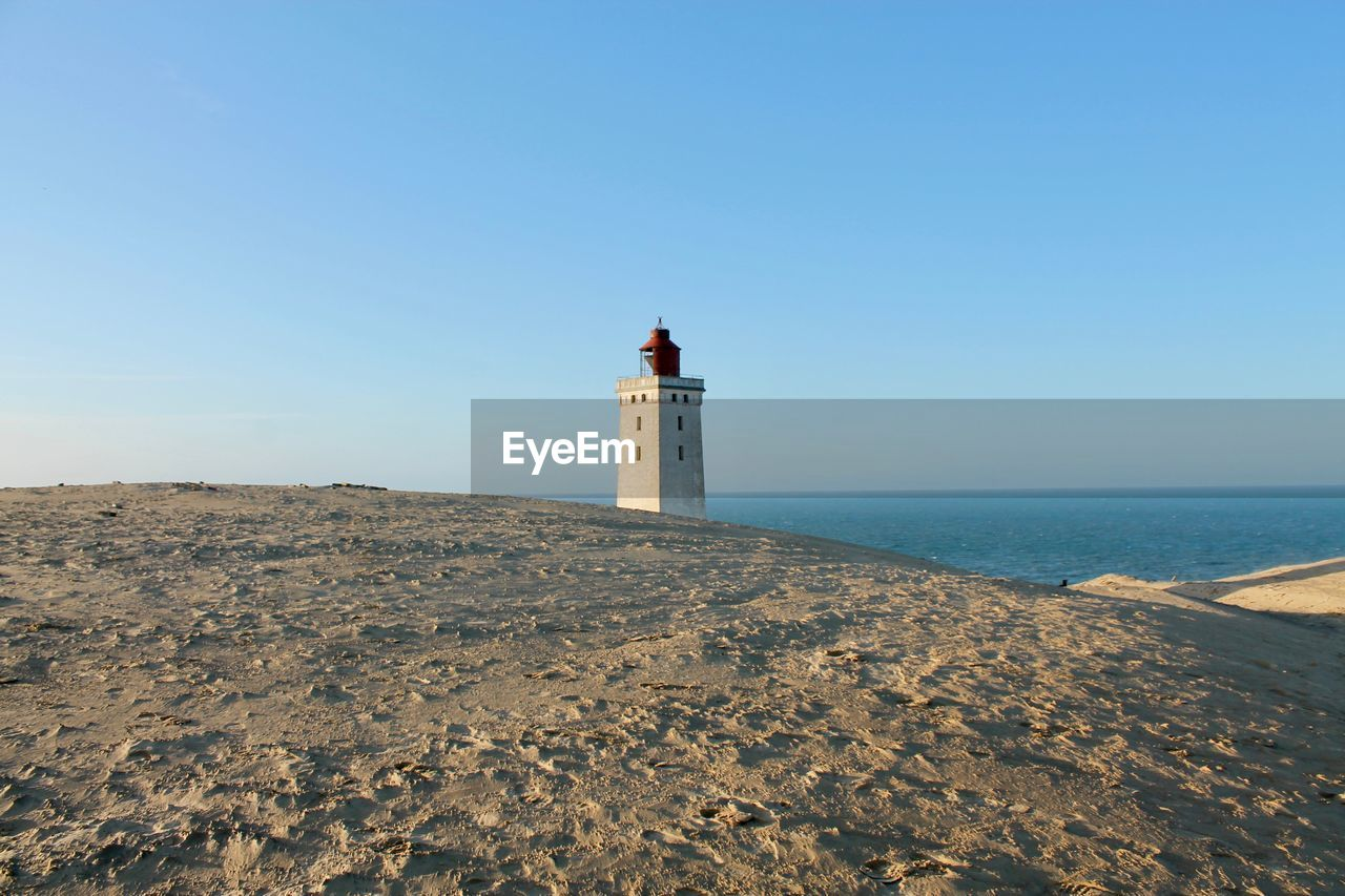 lighthouse, guidance, sky, protection, security, safety, built structure, architecture, sea, tower, direction, building exterior, water, building, clear sky, land, beach, scenics - nature, nature, no people, horizon over water, outdoors, buried