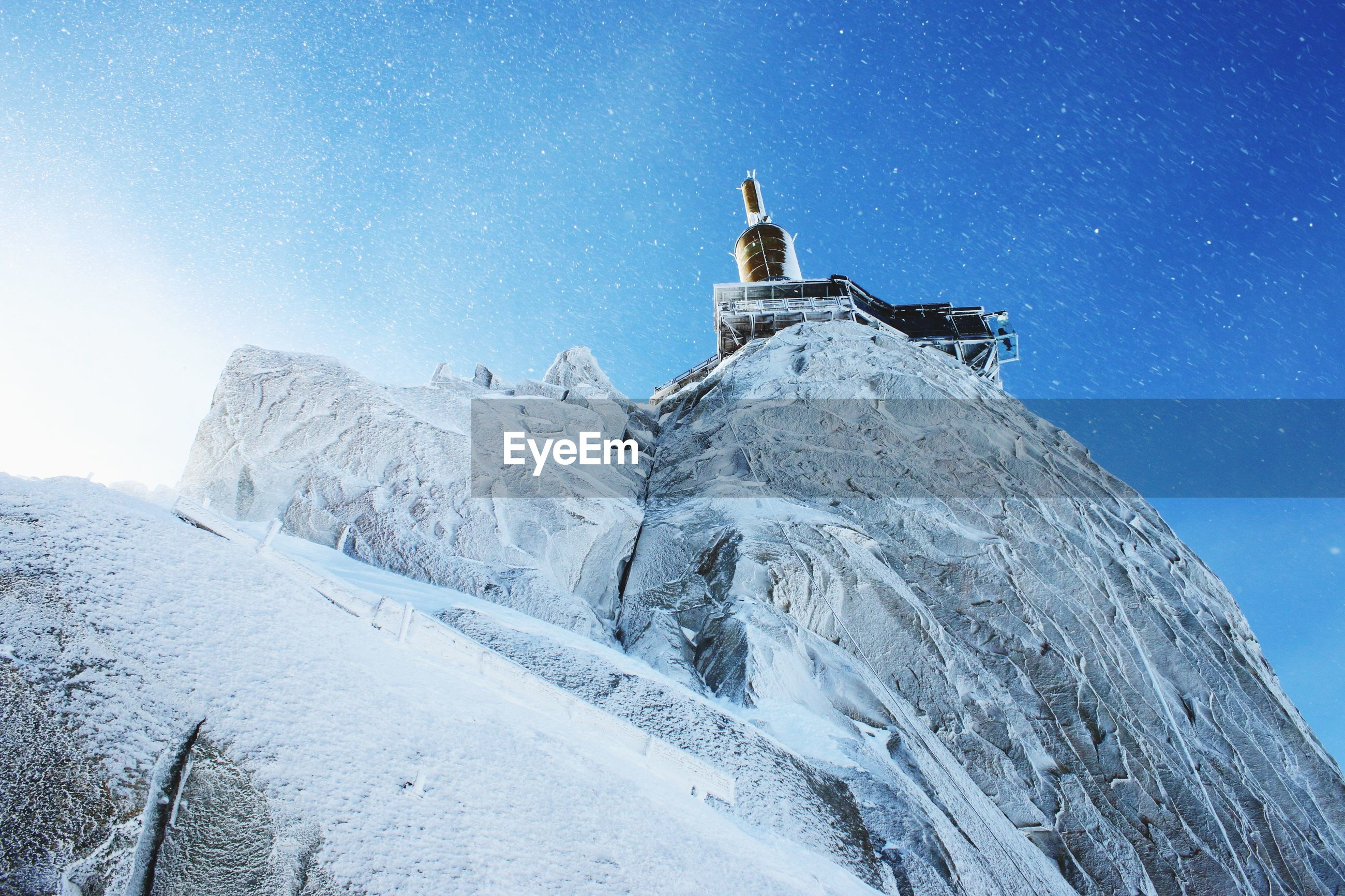 Low angle view of aiguille du midi in snow against blue sky