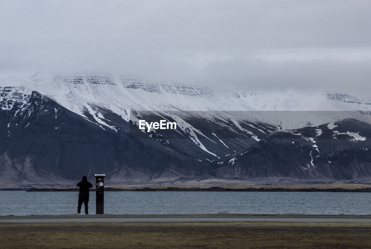 PEOPLE STANDING ON SNOWCAPPED MOUNTAIN AGAINST SEA