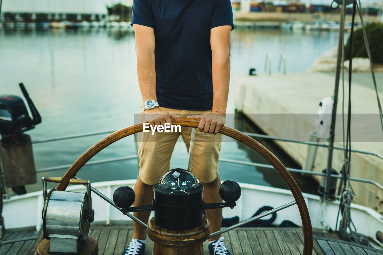 Low section of man holding steering wheel in boat