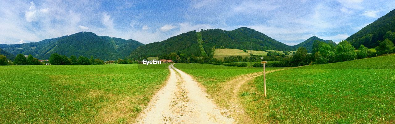 mountain, scenics - nature, plant, landscape, sky, tranquil scene, environment, nature, tranquility, beauty in nature, grass, mountain range, green color, land, road, field, tree, cloud - sky, rural scene, no people, outdoors