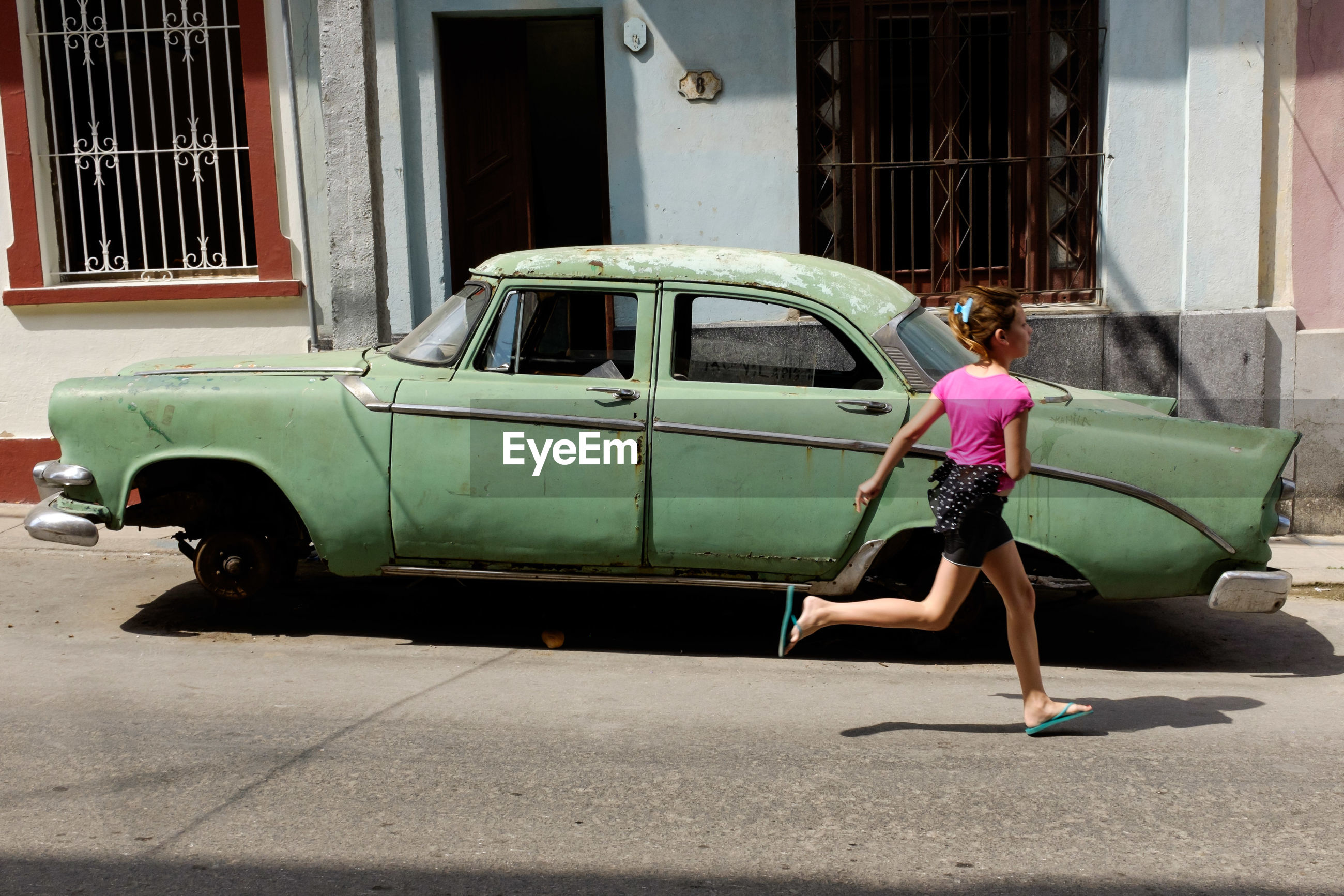 REAR VIEW OF WOMAN ON STREET AGAINST CAR